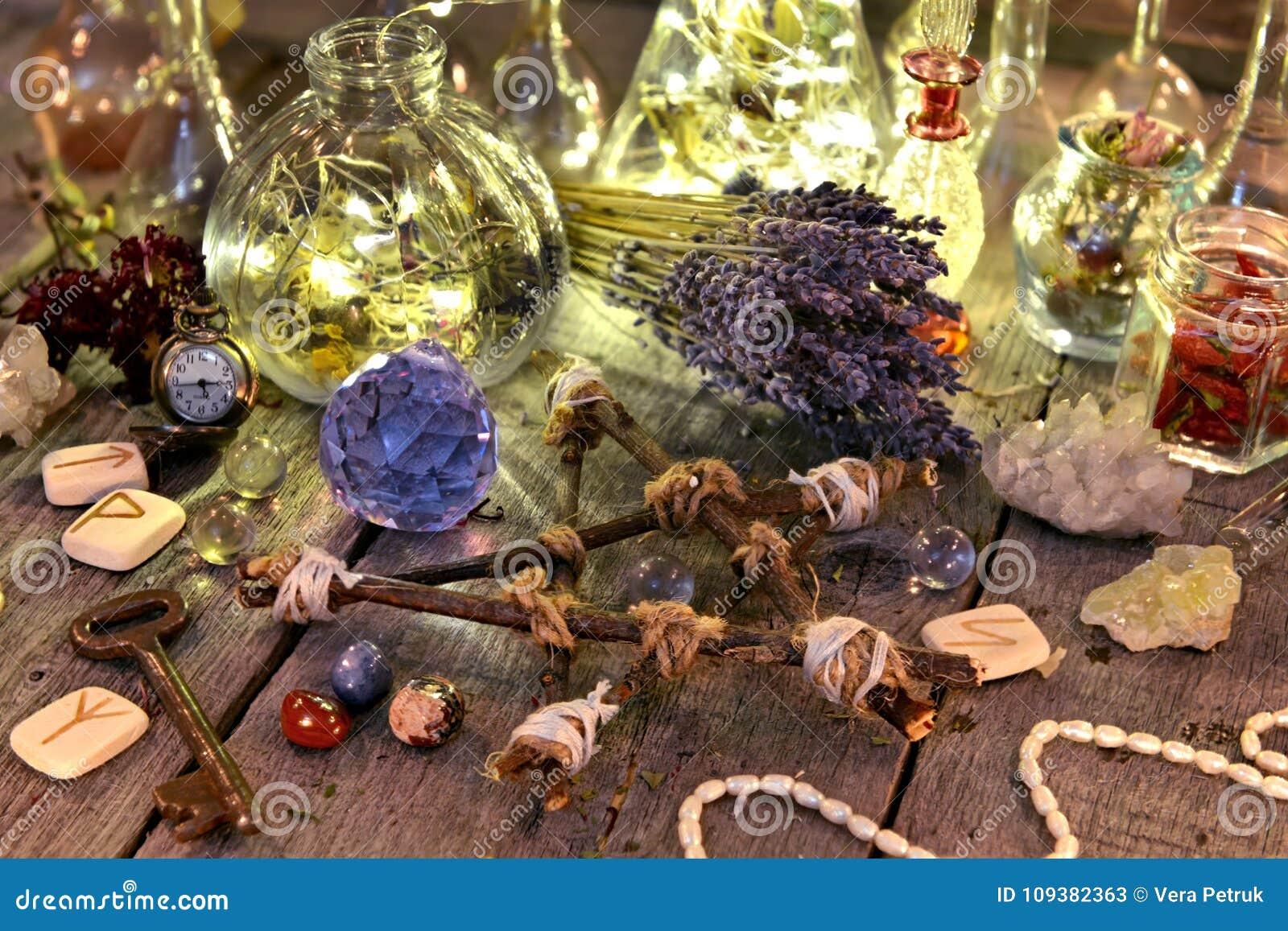 De magische rituele inzameling met flessen, lavendel bloeit, pentagram, runen en kristallen