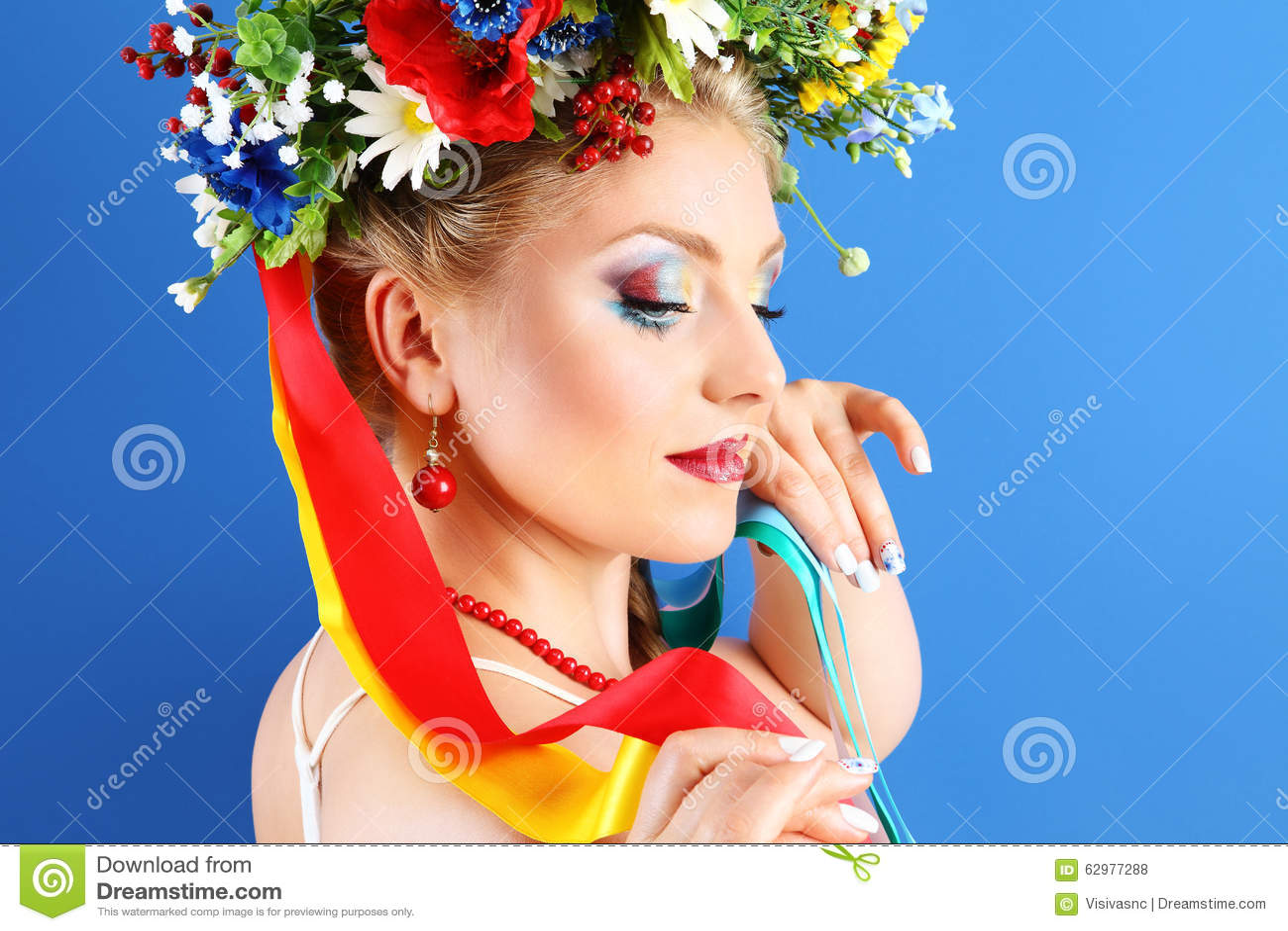 De make-up van de portretvrouw met bloemen op blauwe achtergrond