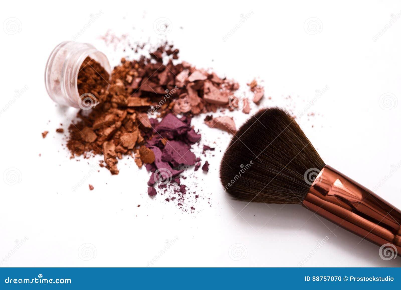 De make-upborstels met blozen of oogschaduw van roze, rood en koraaltonen op witte achtergrond wordt bestrooid die