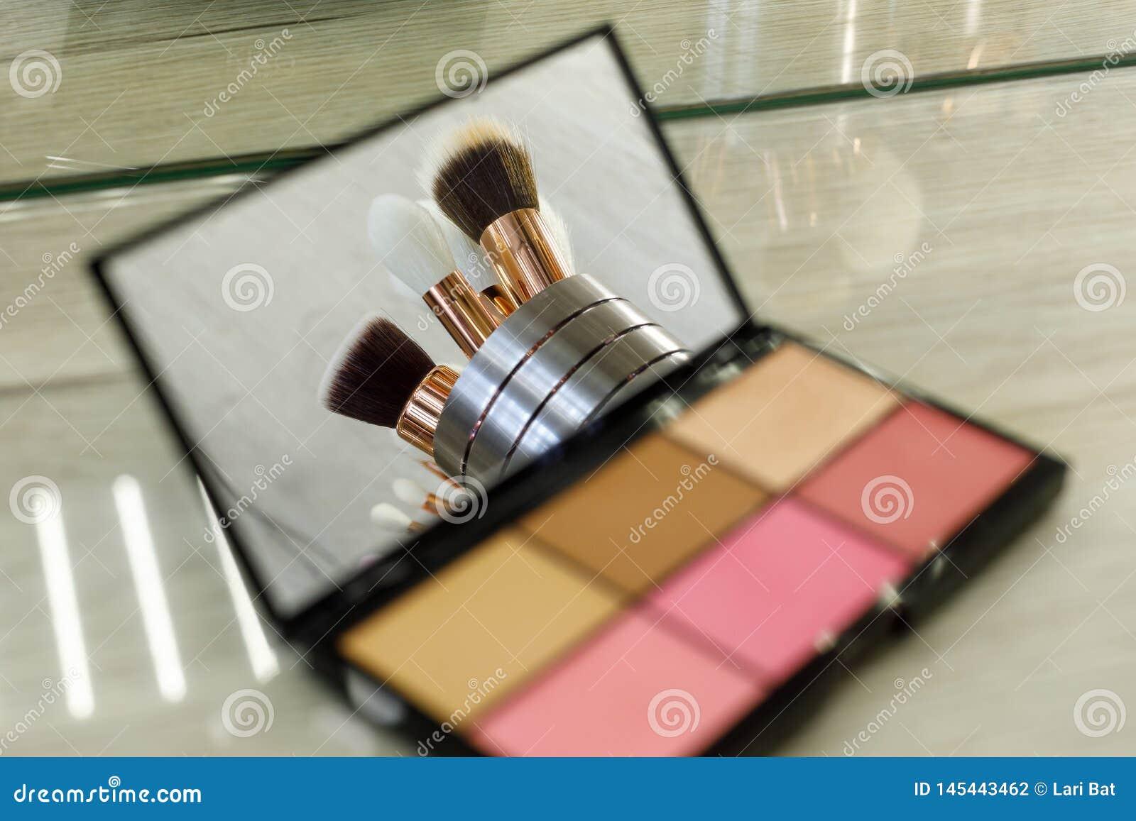 De make-upborstels worden weerspiegeld in een paletspiegel met schaduwen