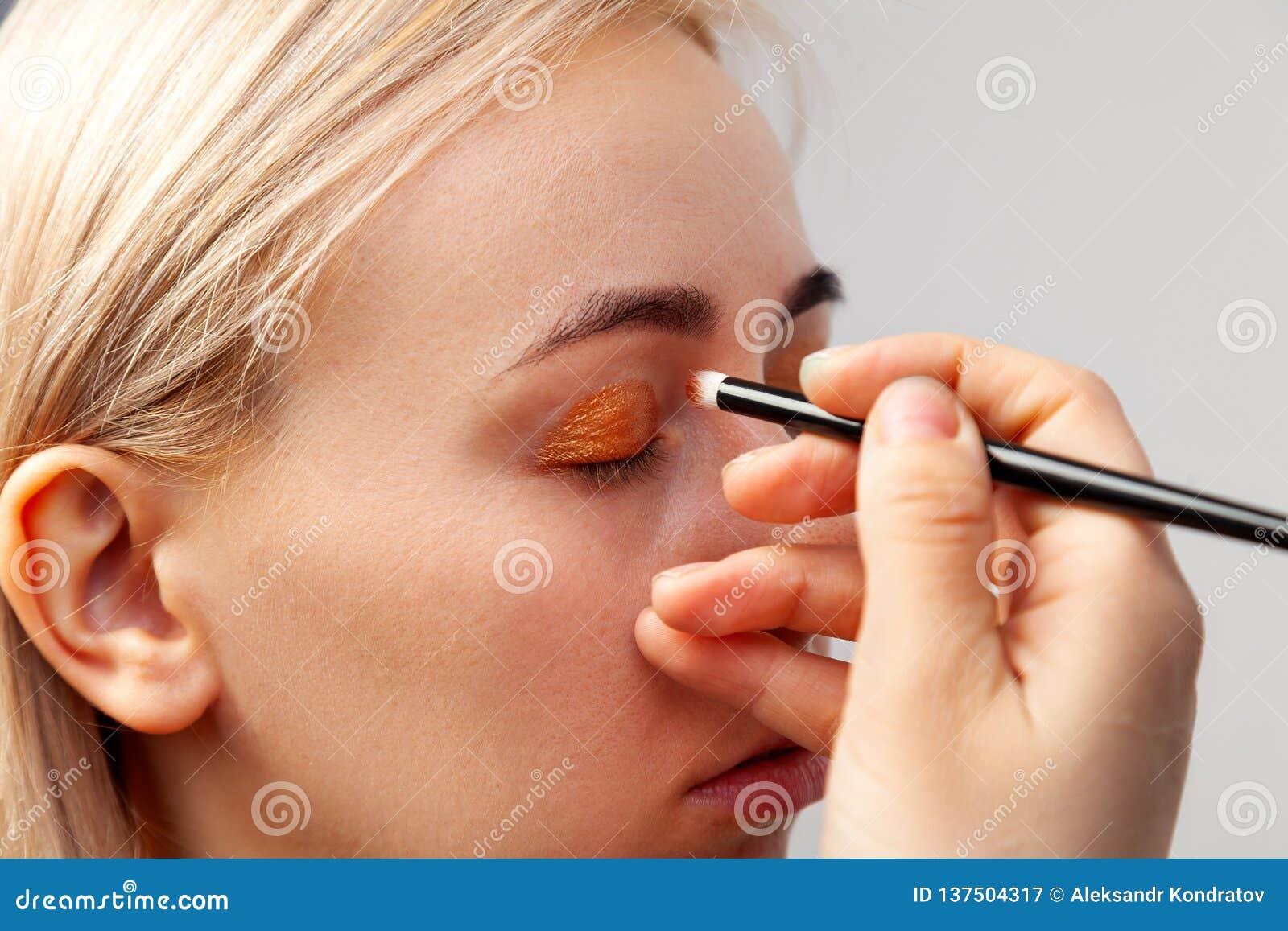 De make-upkunstenaar met een borstel in zijn hand zette op dichte gouden schaduwen op de oogleden