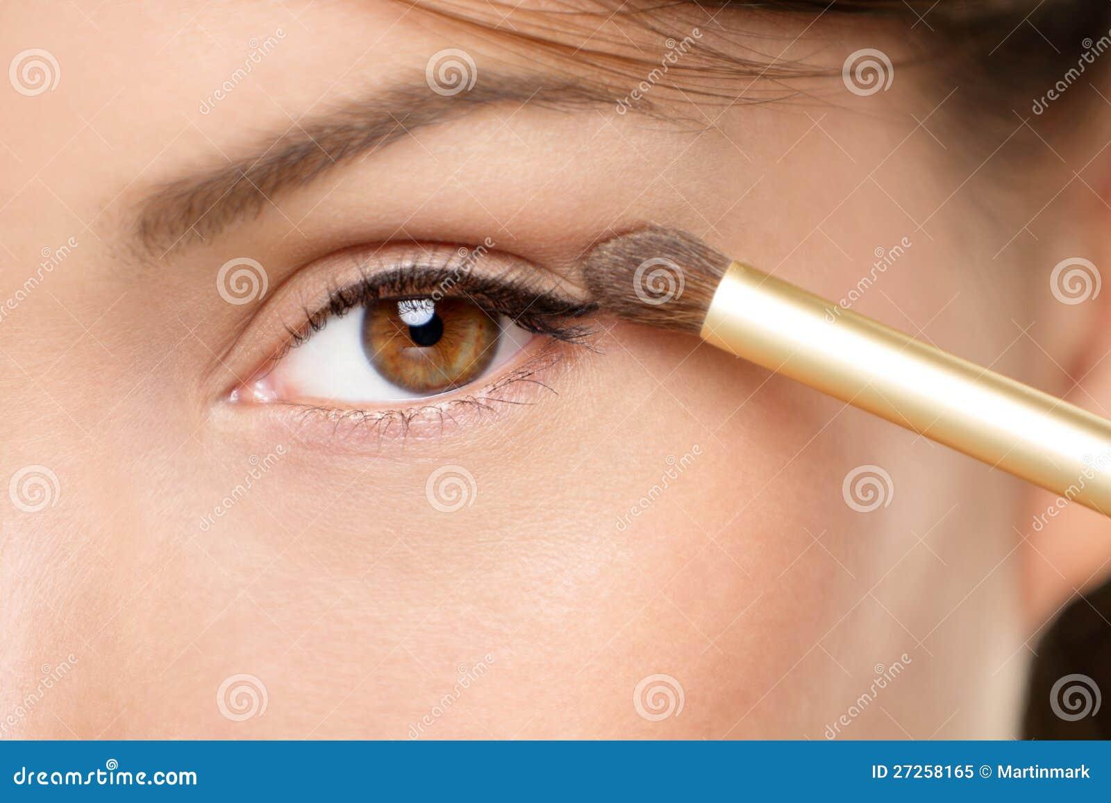 De make-upvrouw die van het oog oogschaduwpoeder toepast