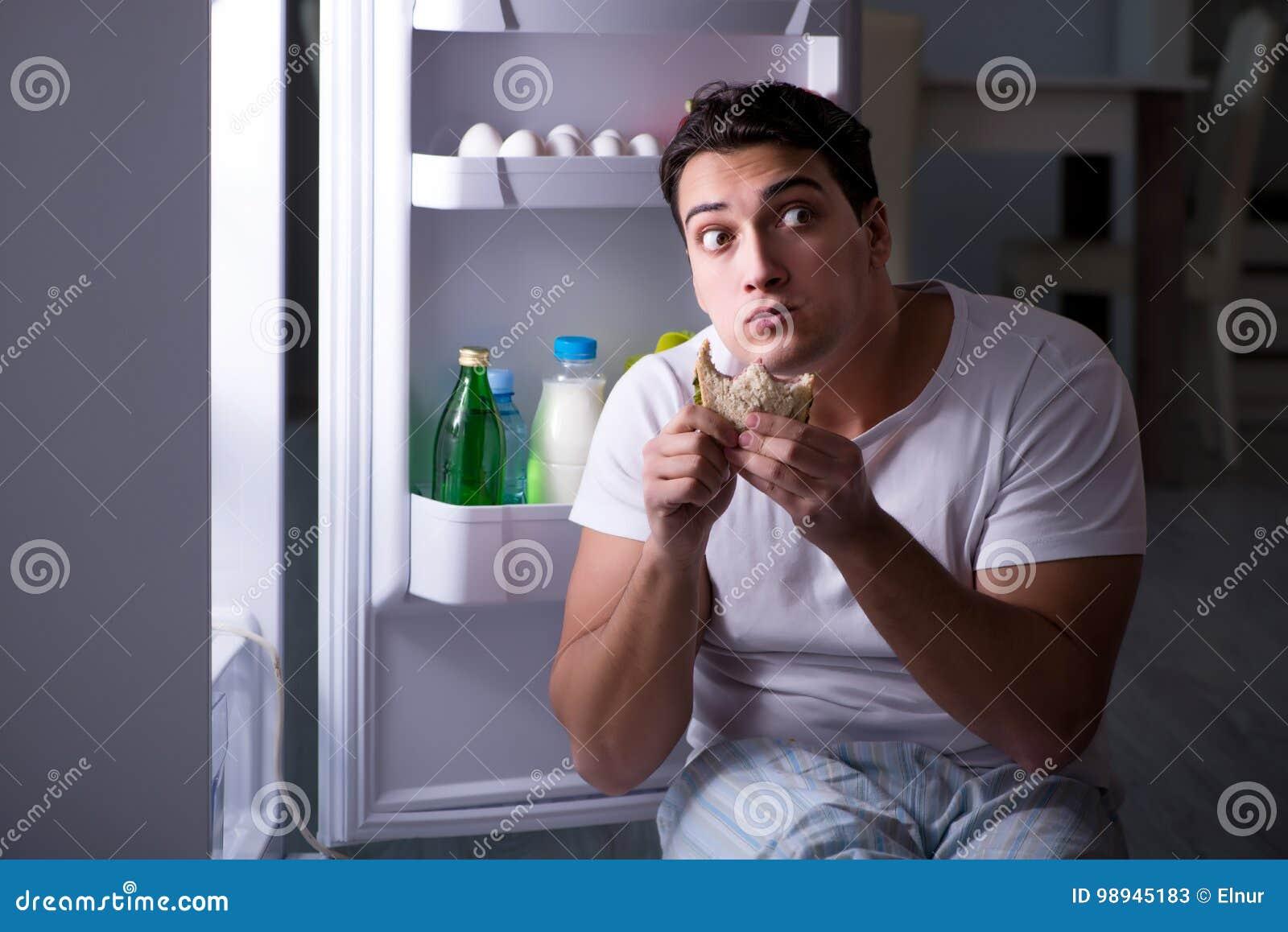 De man bij de koelkast die bij nacht eten