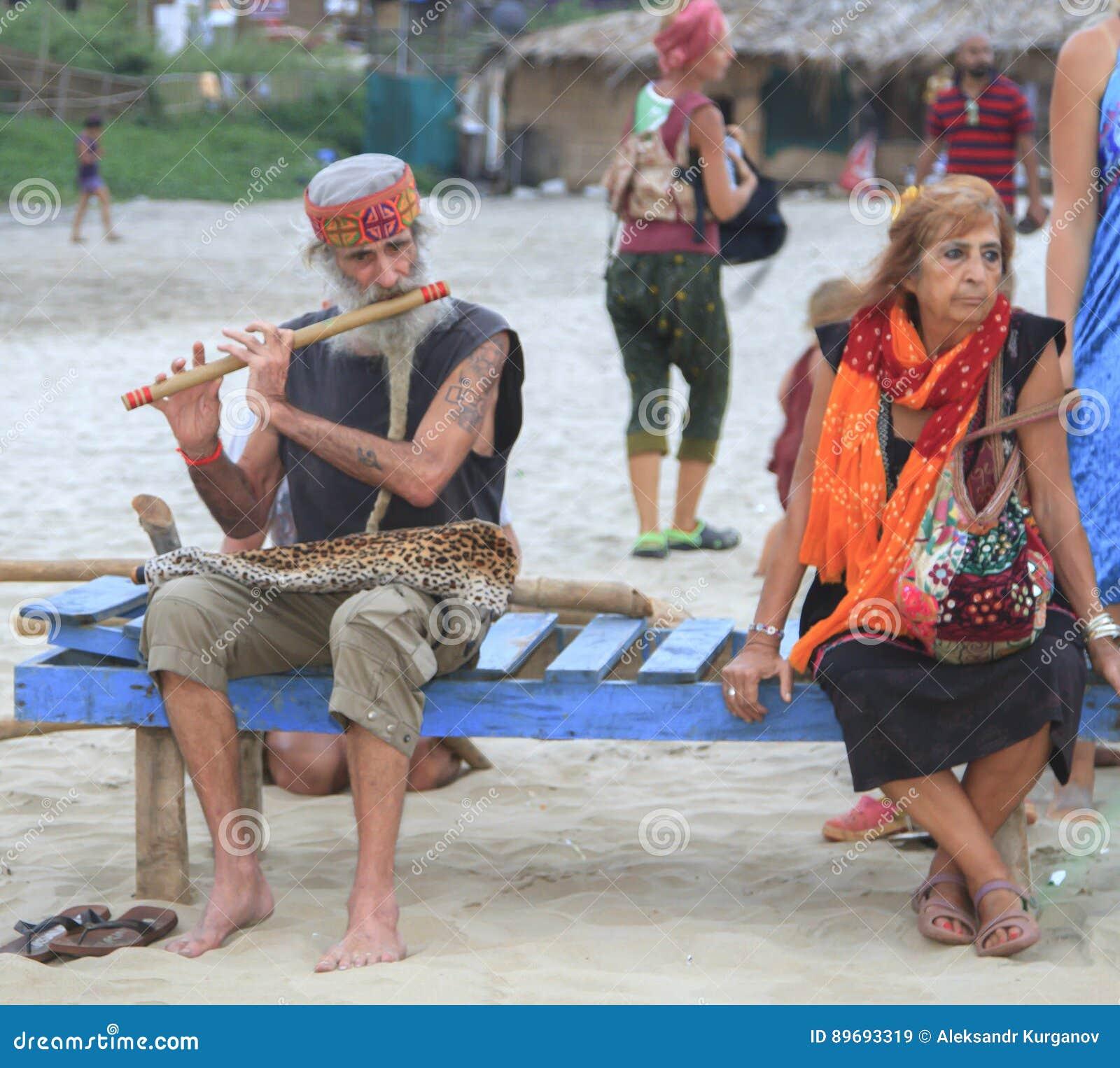 De man die de fluitzitting op het strand in het bedrijf spelen van