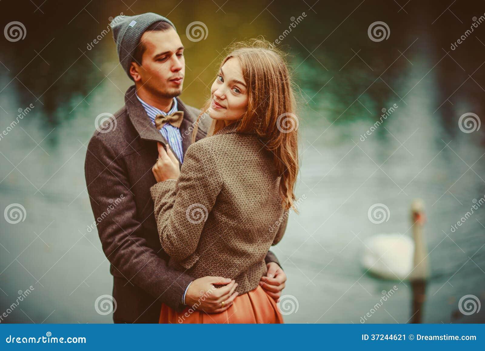 De man en de vrouw die dichtbij meer koesteren