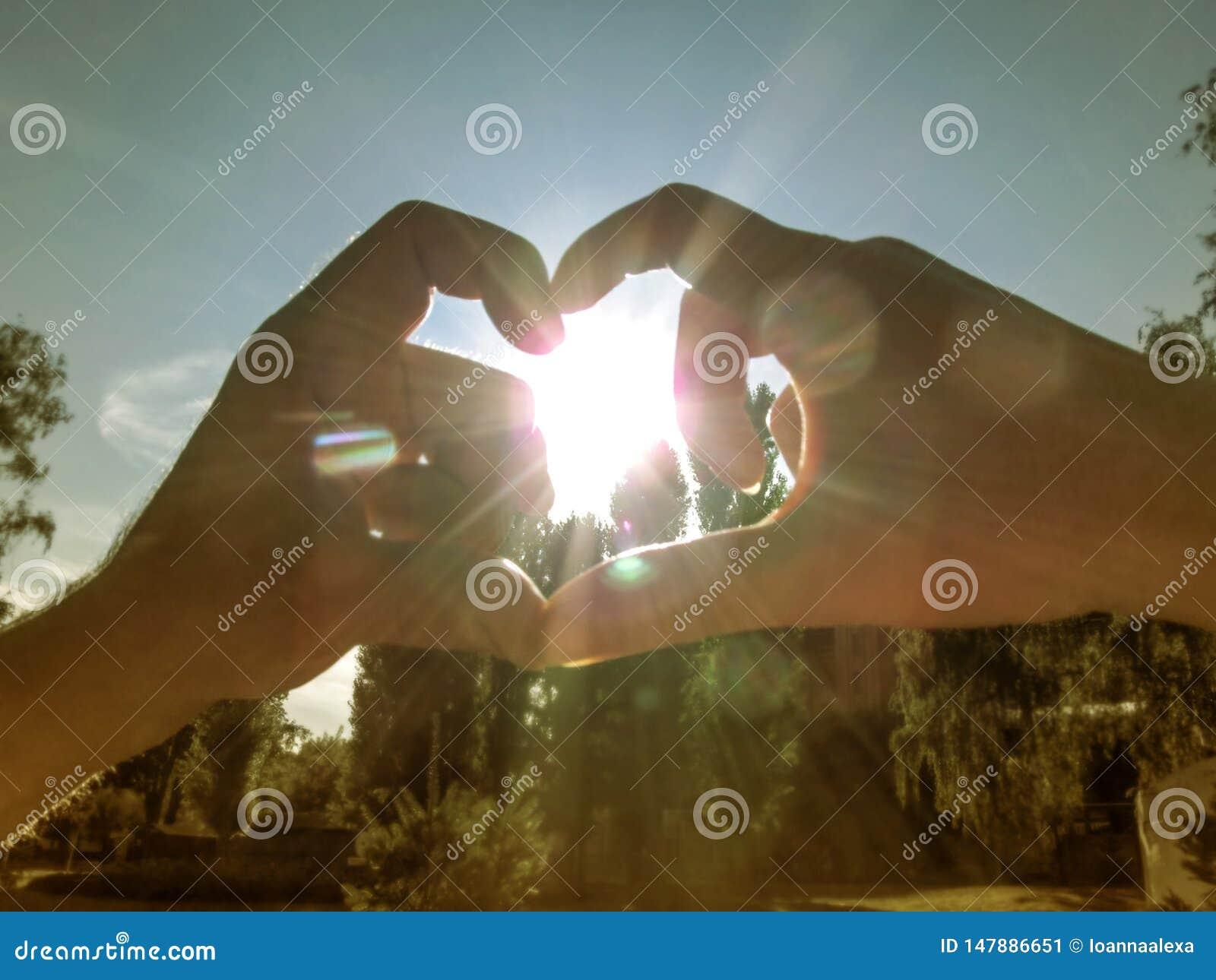 De man en de vrouw maken een hart rond de zon met hun handen Het mannetje en het wijfje dienen de stralen in en de glans van de z