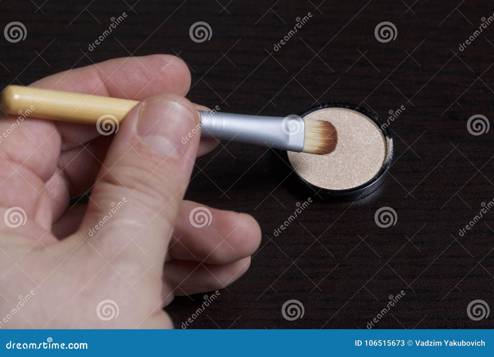 De man houdt een borstel om schoonheidsmiddelen toe te passen Het wordt verminderd door een uiteinde in een ronde container met e