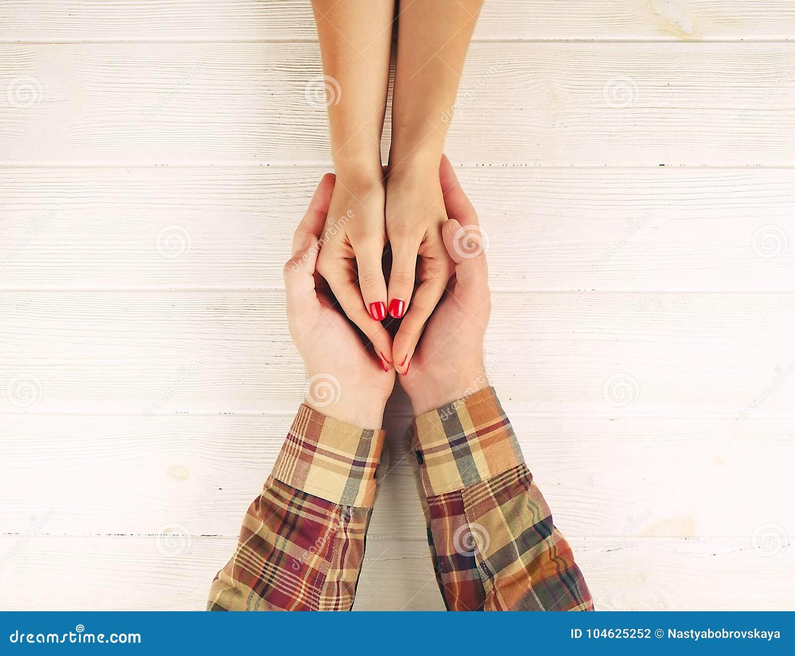Download De Man Houdt Hoogste De Meningsbeeld Van Vrouwen` S Handen Op Witte Houten Achtergrond Paar In Liefdeconcept Stock Foto - Afbeelding bestaande uit hart, gevoel: 104625252