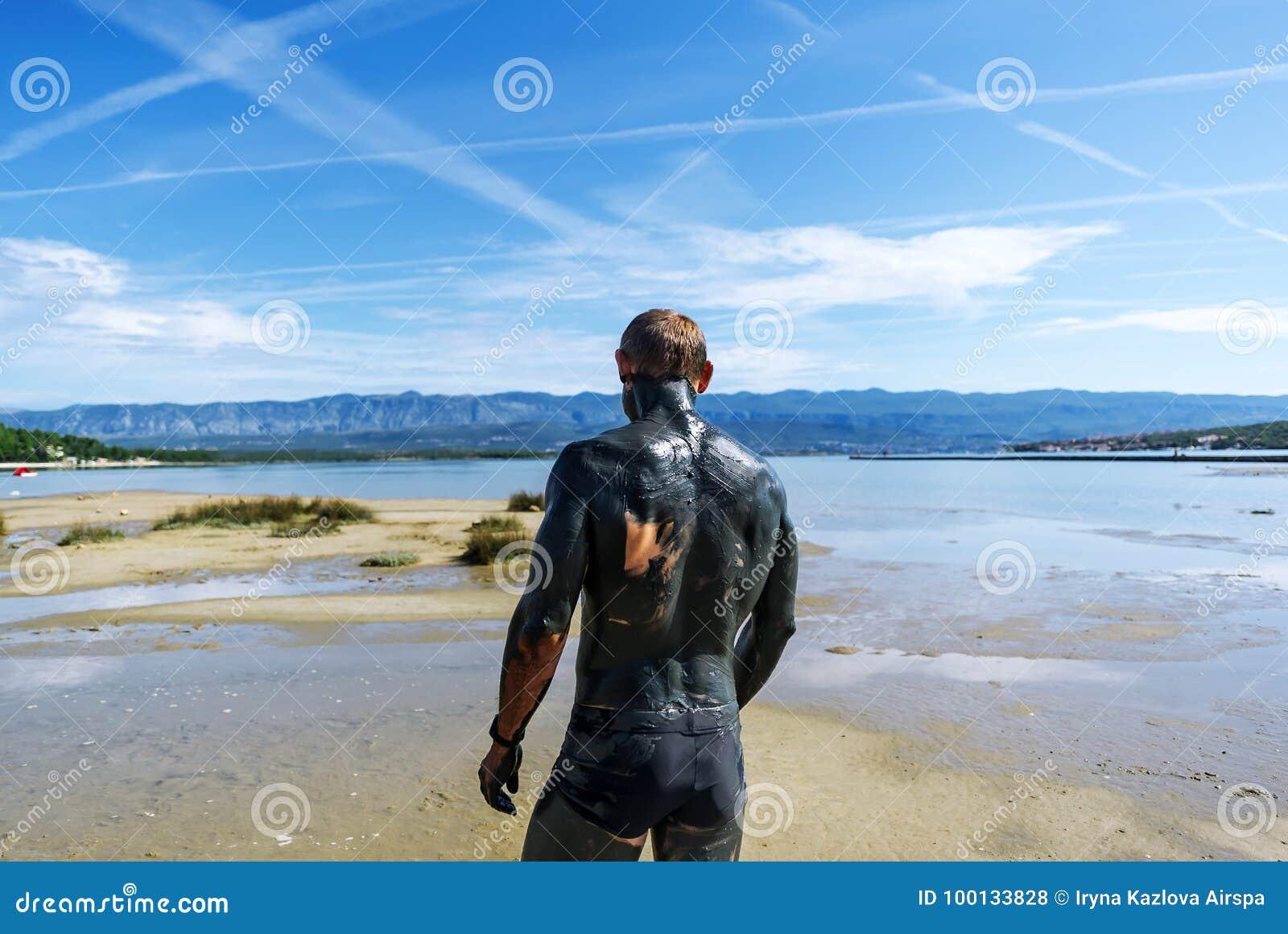 De man omvat met therapeutische modder loopt op het strand