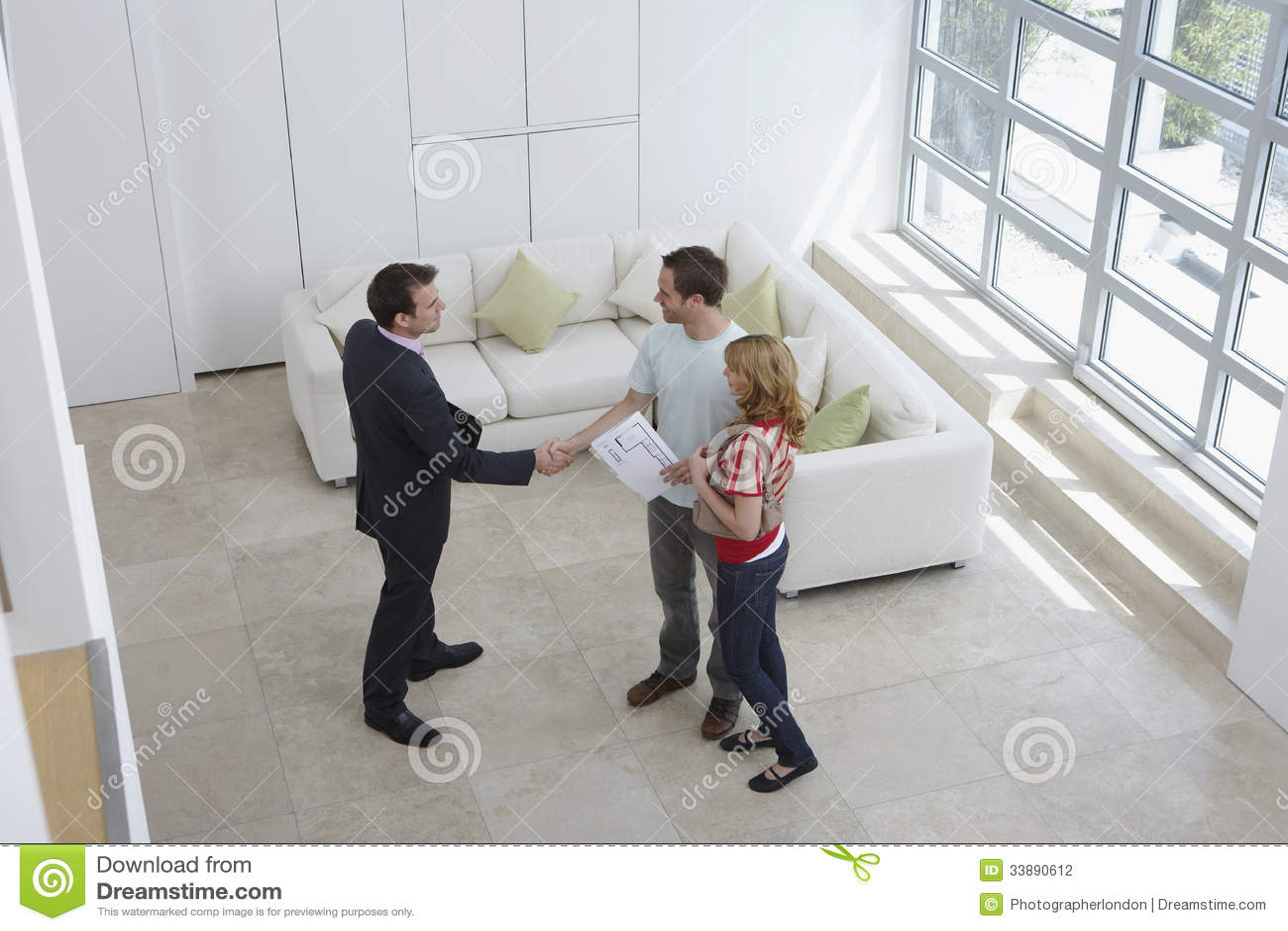 De Man van makelaar in onroerend goedshaking hands with door Vrouw in Nieuw Huis