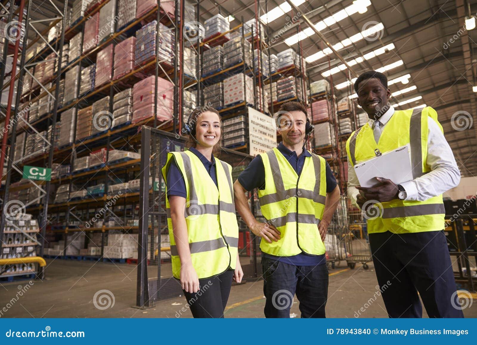 De manager en de collega s van het distributiepakhuis kijken aan camera