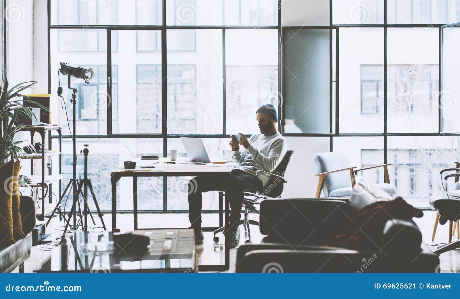 De manager van de foto het gebaarde rekening oped werken met nieuw project ruimtezolderstudio Kijkend moderne smartphone eigentij