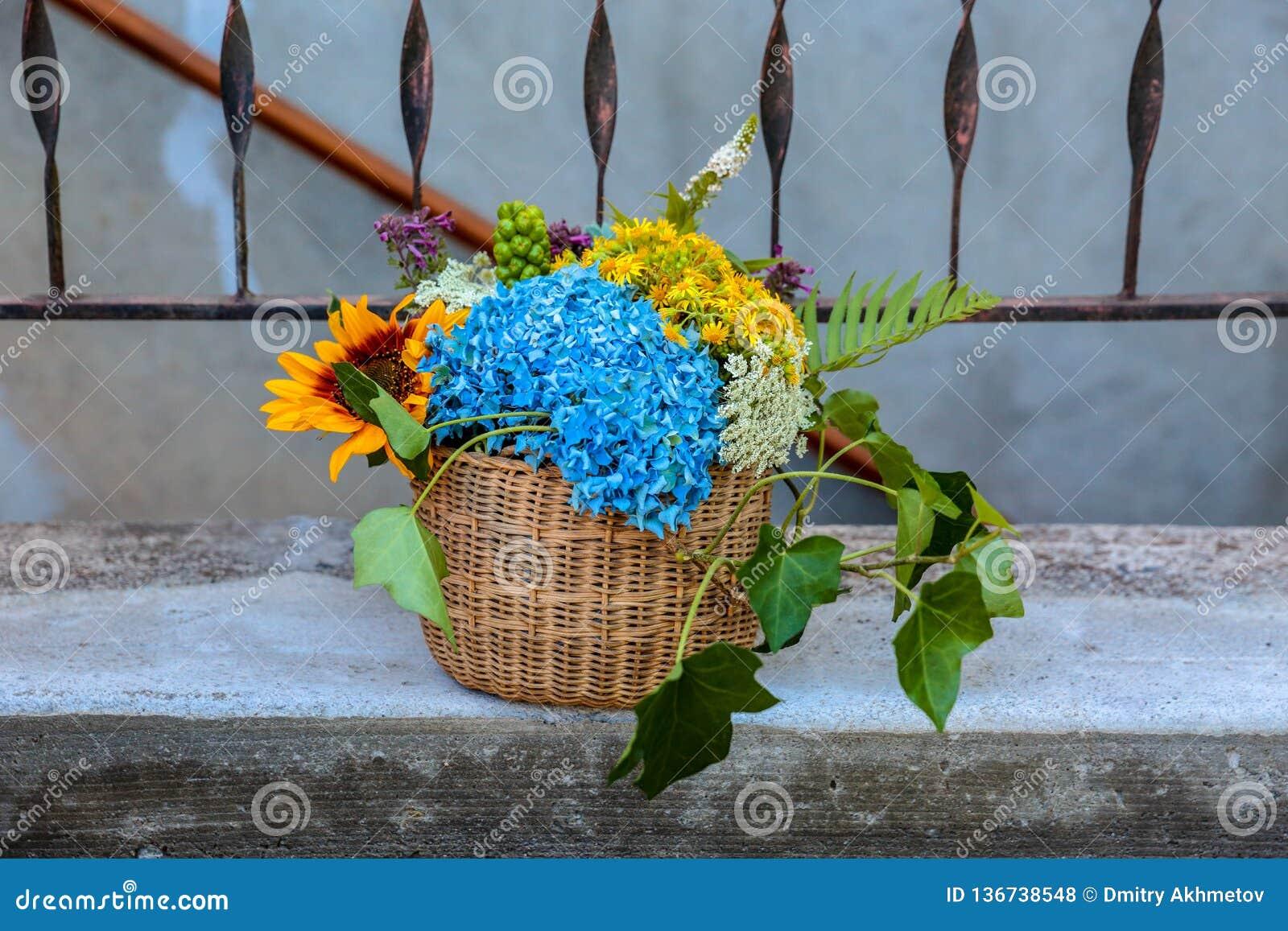 De mandmand die van huwelijksbloemen zich op een portiek van een huis bevinden