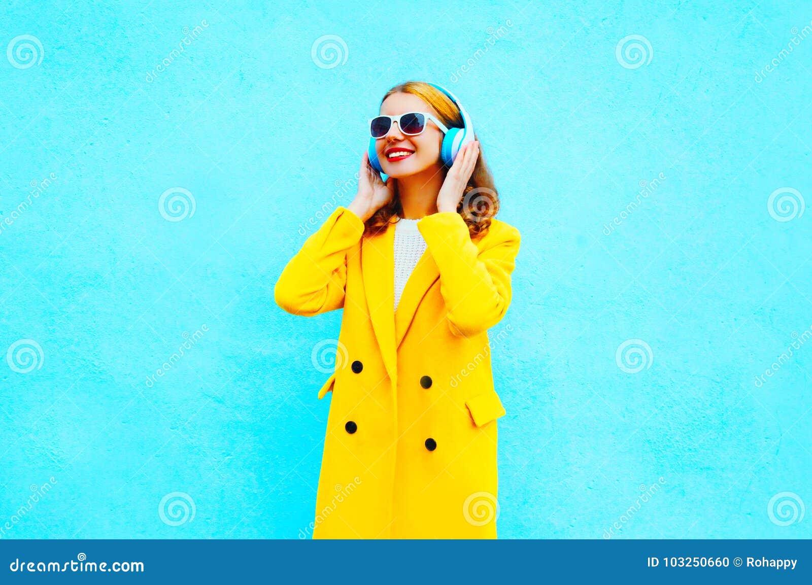 De manier die jonge vrouw glimlachen luistert aan muziek in hoofdtelefoons