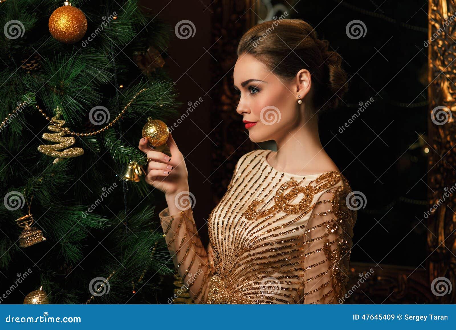 De maniervrouw hing een stuk speelgoed op de Kerstboom