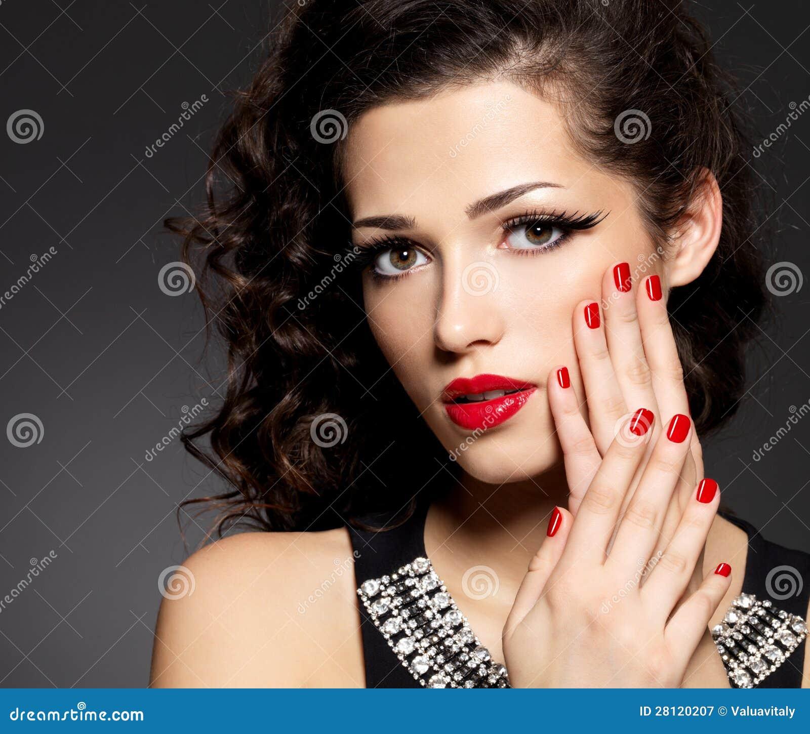De maniervrouw van de schoonheid met rode spijkers en make-up