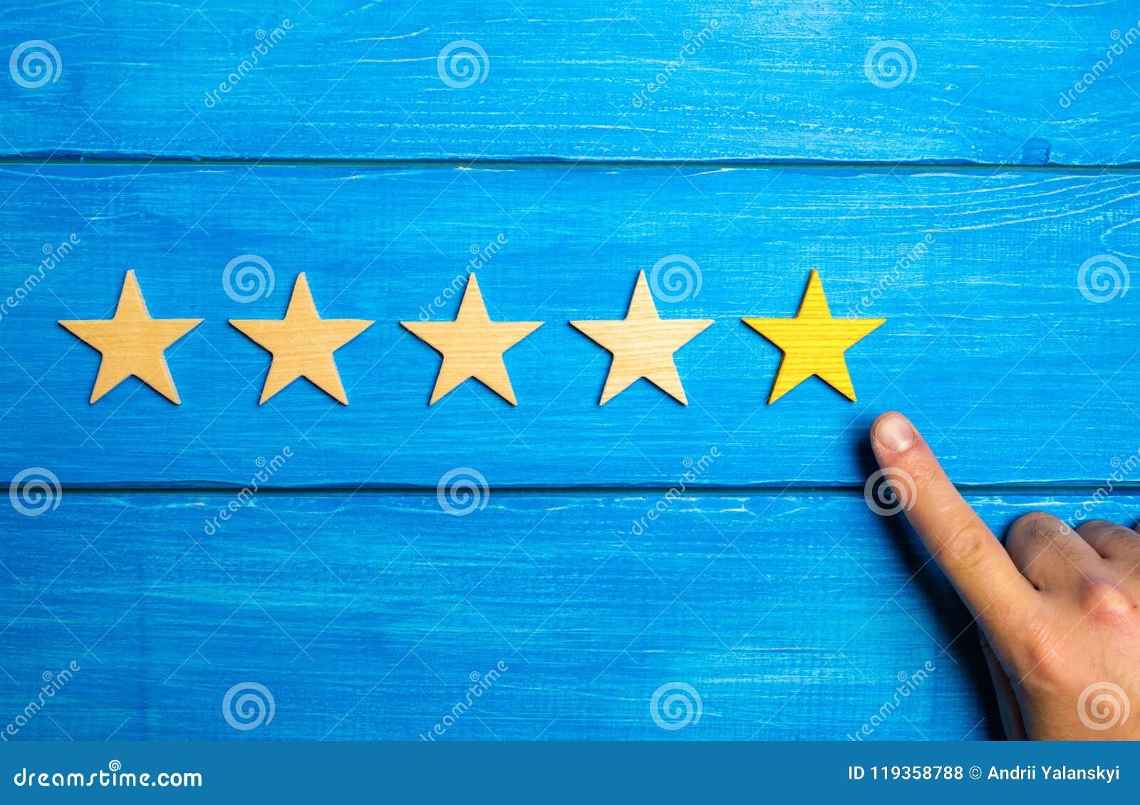 De manliga handpunkterna till den femte gula stjärnan på en blå träbakgrund fem stjärnor Värdering av restaurangen eller hotellet