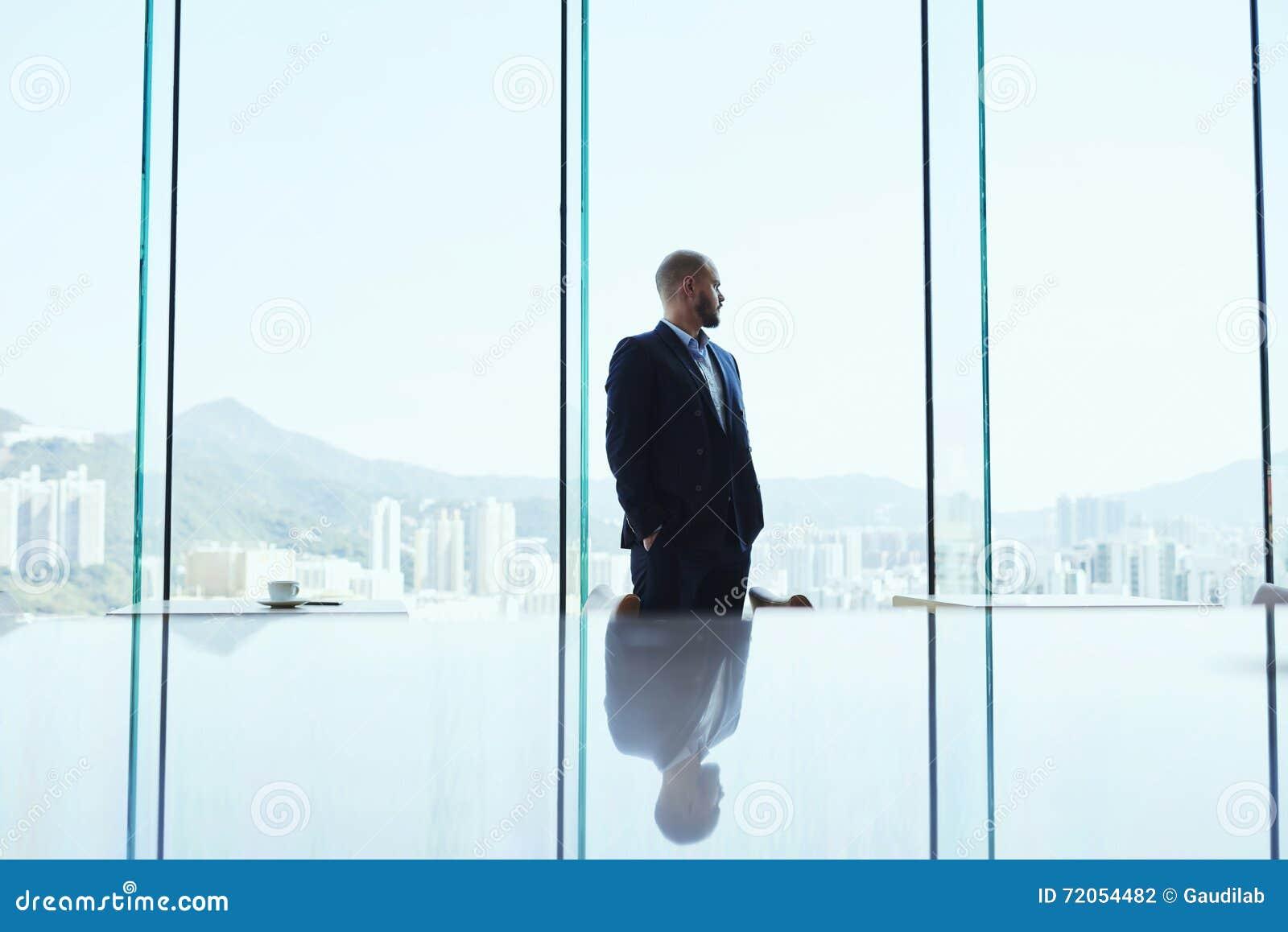 De mannelijke bankier bevindt zich in modern bureaubinnenland en let op in venster op bedrijfsdistrict