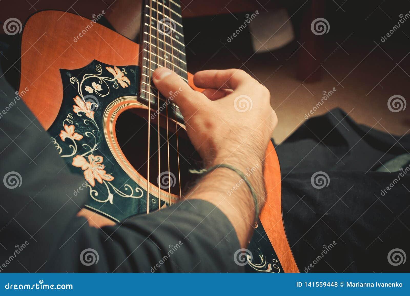 De mannelijke hand speelt de koorden van het oude gitaarclose-up