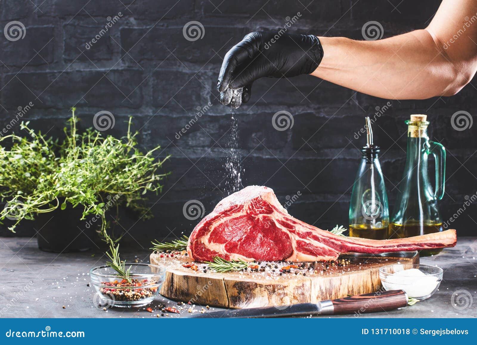 De mannelijke handen van slager of kok het rundvleeslapje vlees van de holdingstomahawk op donkere rustieke keuken dienen achterg