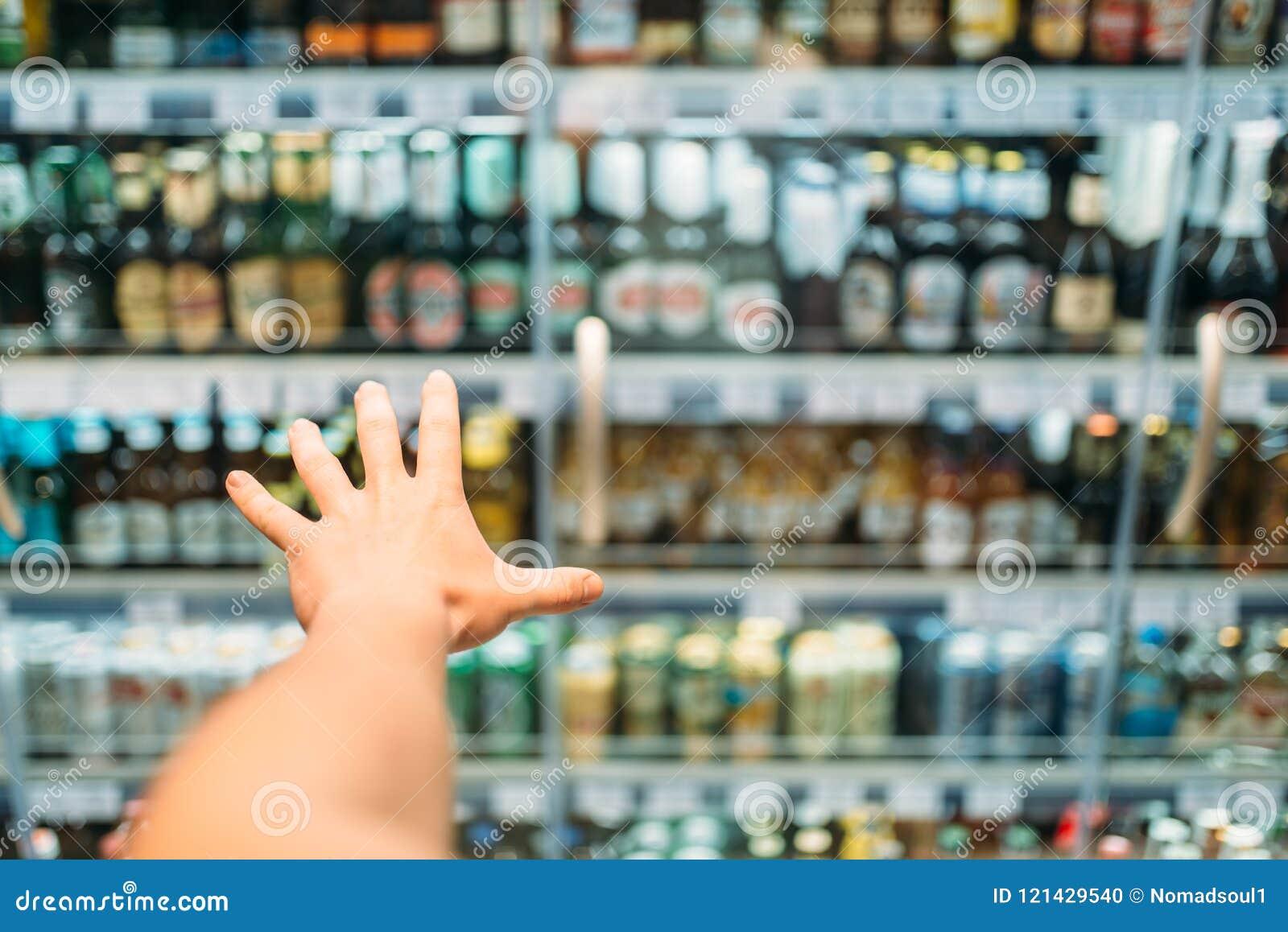 De mannelijke klantenhand bereikt voor alcoholische producten