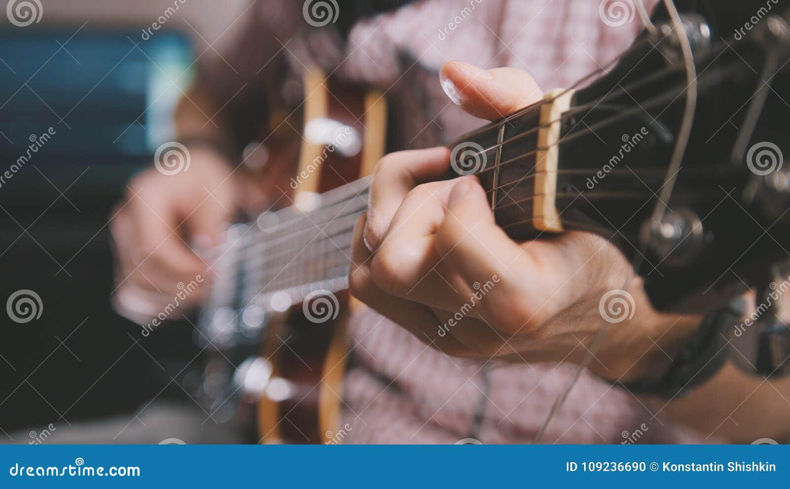 De mannelijke musicus speelt de gitaar, dicht omhoog overhandigt