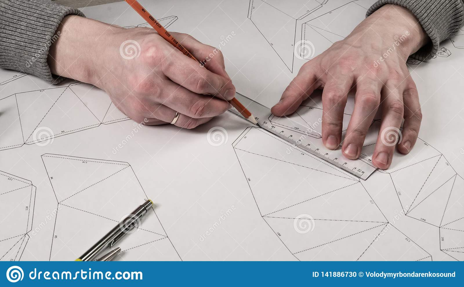 De mannelijke ontwerper maakt een werkende tekening Werkplaats van een stuk speelgoed ontwerper De tellers, de heerser, de pen en