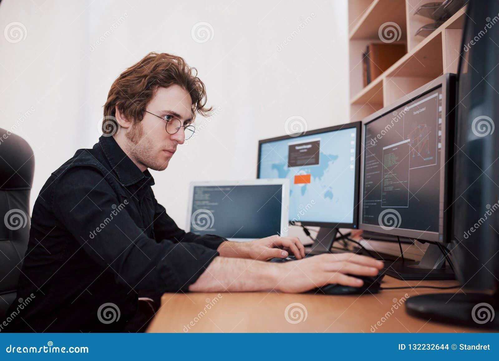 De mannelijke programmeur die aan bureaucomputer met vele monitors op kantoor in software werken ontwikkelt bedrijf Websiteontwer