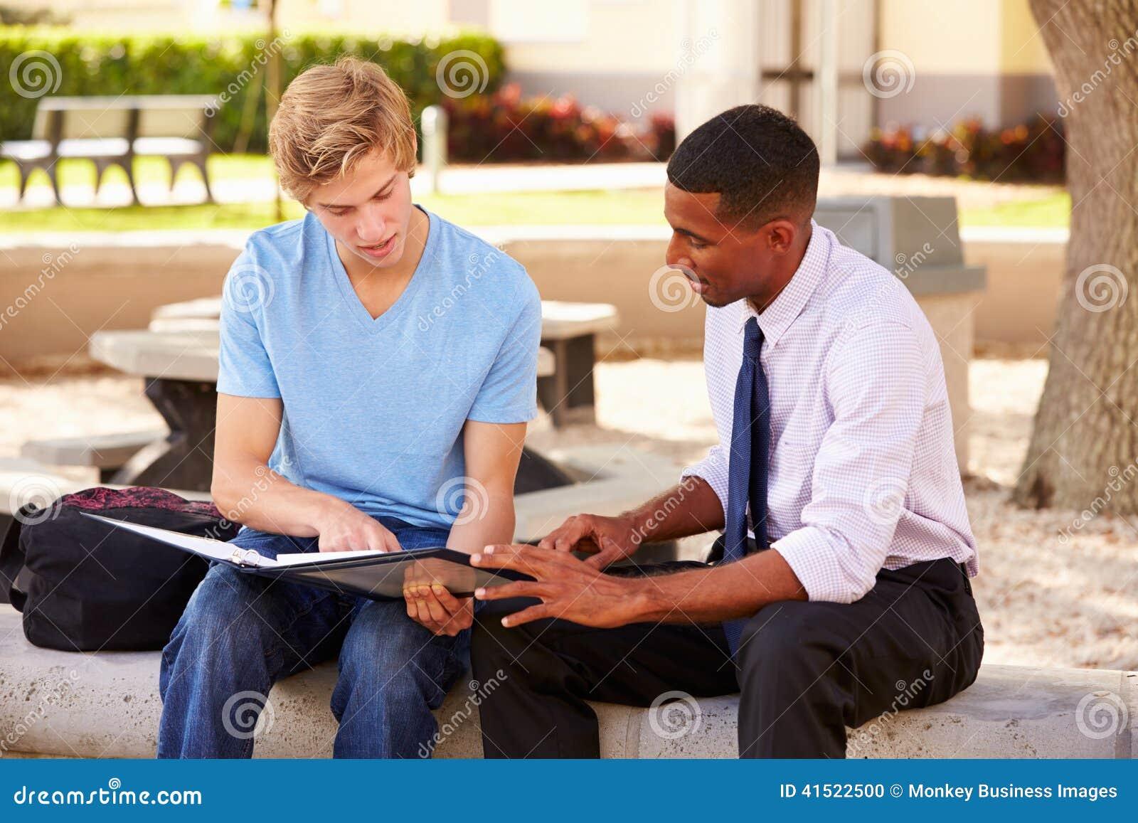 De Mannelijke Student With Work van leraarssitting outdoors helping