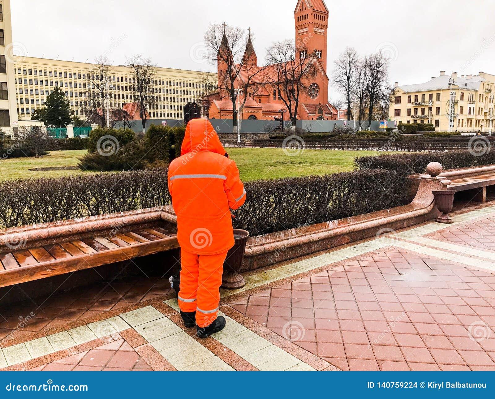 De mannelijke werkende reinigingsmachine in oranje overall die robekleren dragen die maakt de straten van de stad schoon werken