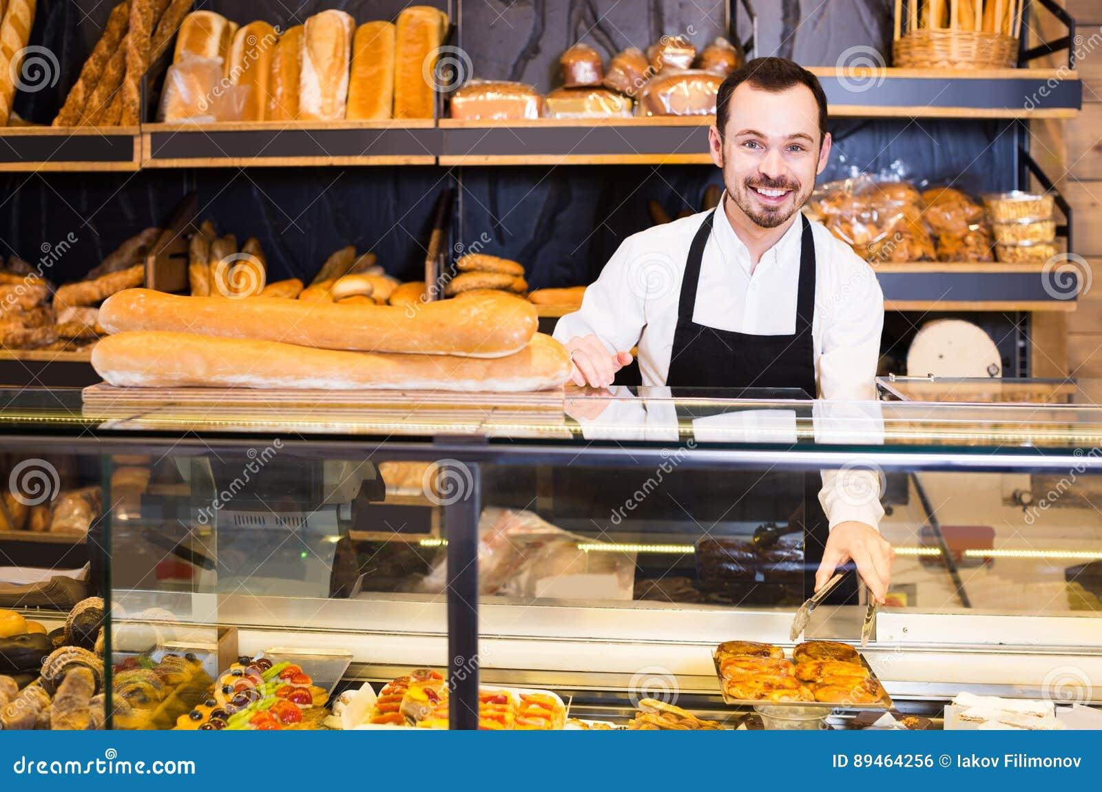 De mannelijke winkelmedewerker die vers heerlijk gebakje aantonen bakt binnen