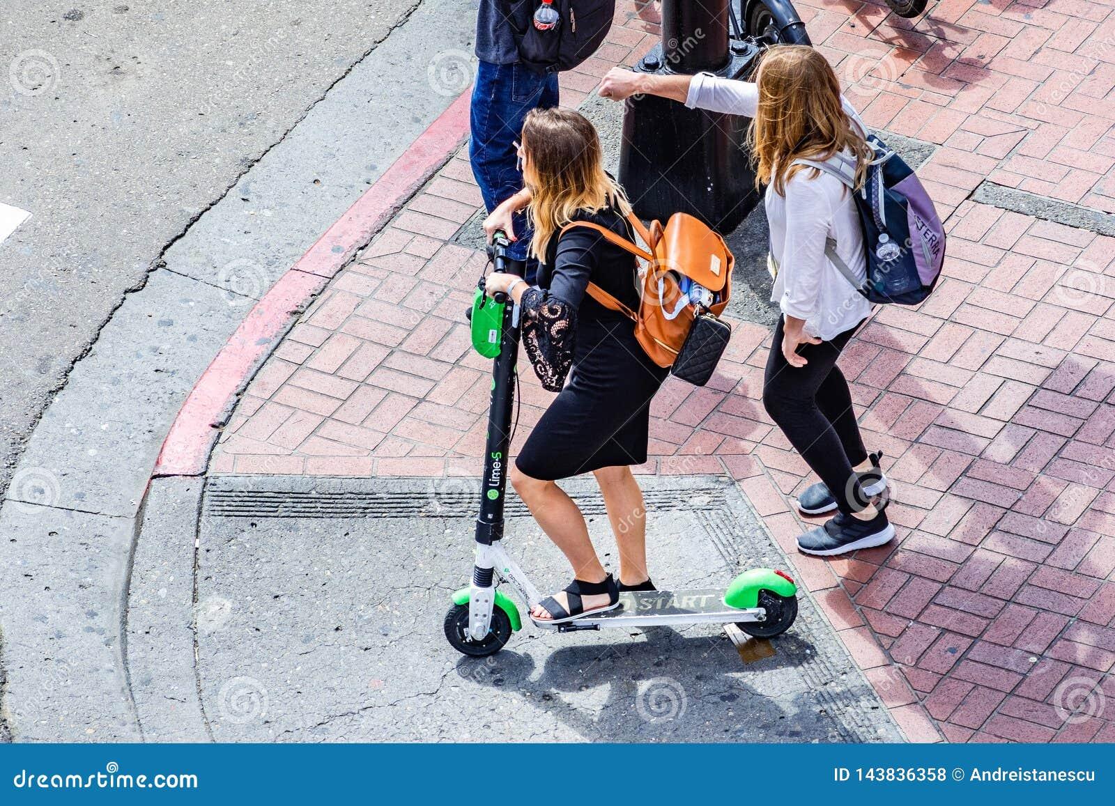 19 de março de 2019 San Diego/CA/EUA - opinião aérea a jovem mulher que monta um  trotinette  do cal em San Diego do centro
