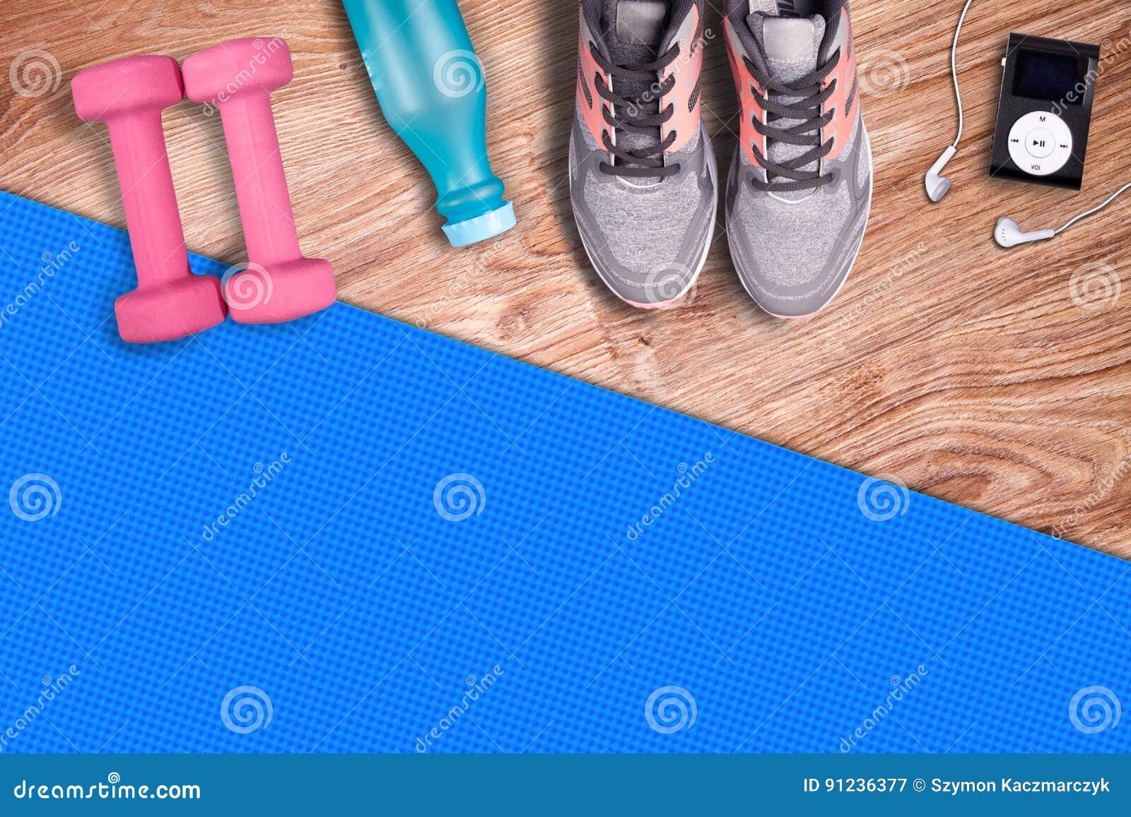 De mat van de geschiktheidsgymnastiek en lichtrose domoren Geschikte materiaalschoenen en muziekspeler