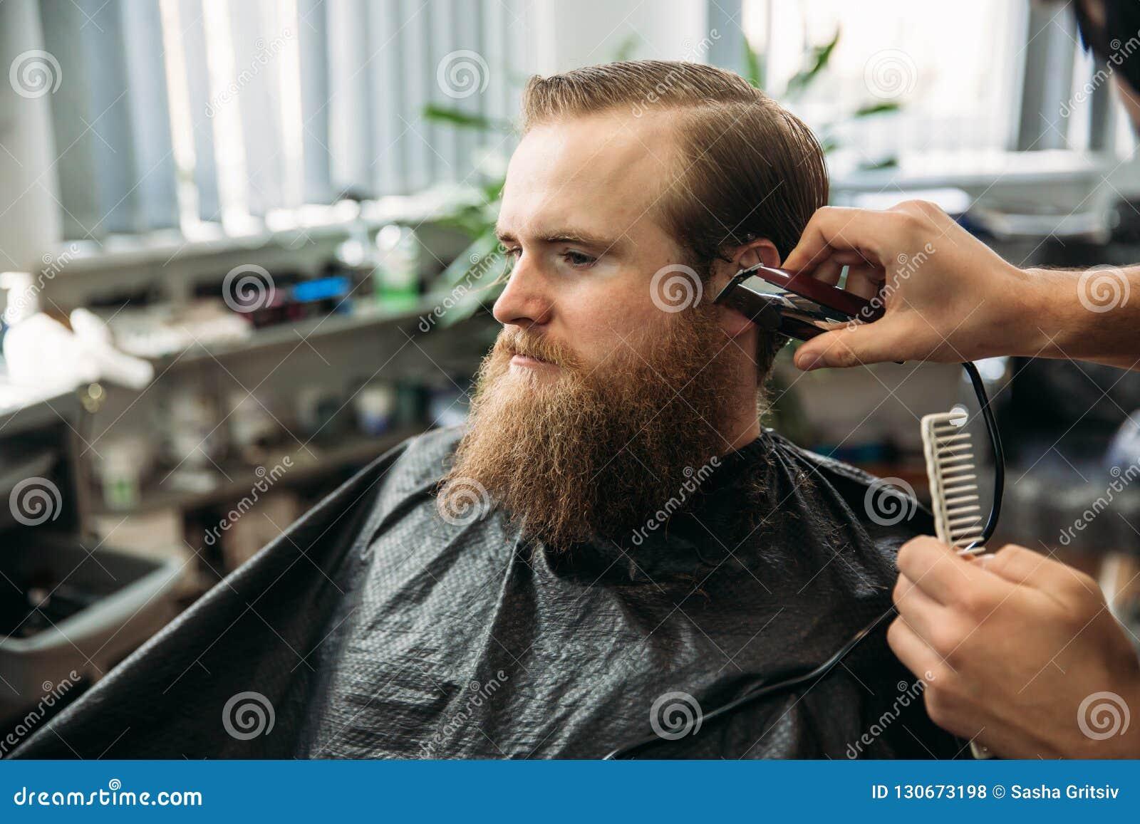 De meester snijdt haar en de baard van mensen in de herenkapper, kapper maakt kapsel voor een jonge mens