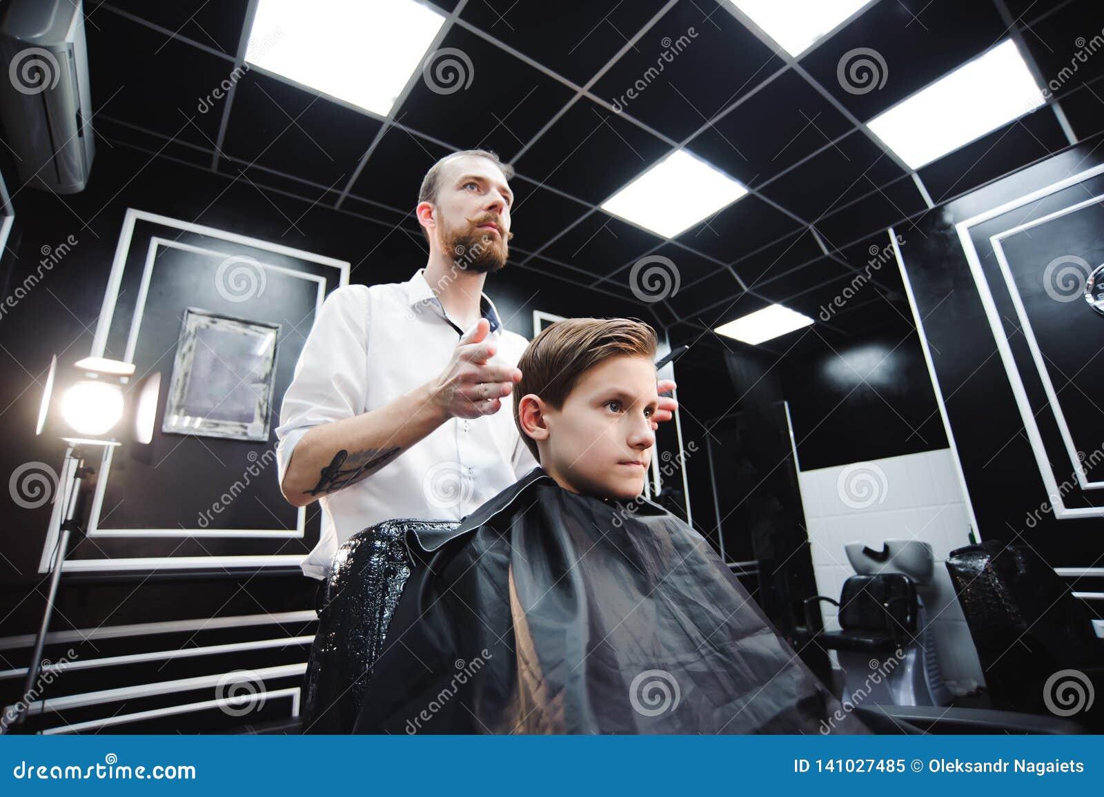 De meester snijdt haar van een jongen in de herenkapper, maakt de kapper kapsel voor een jongen