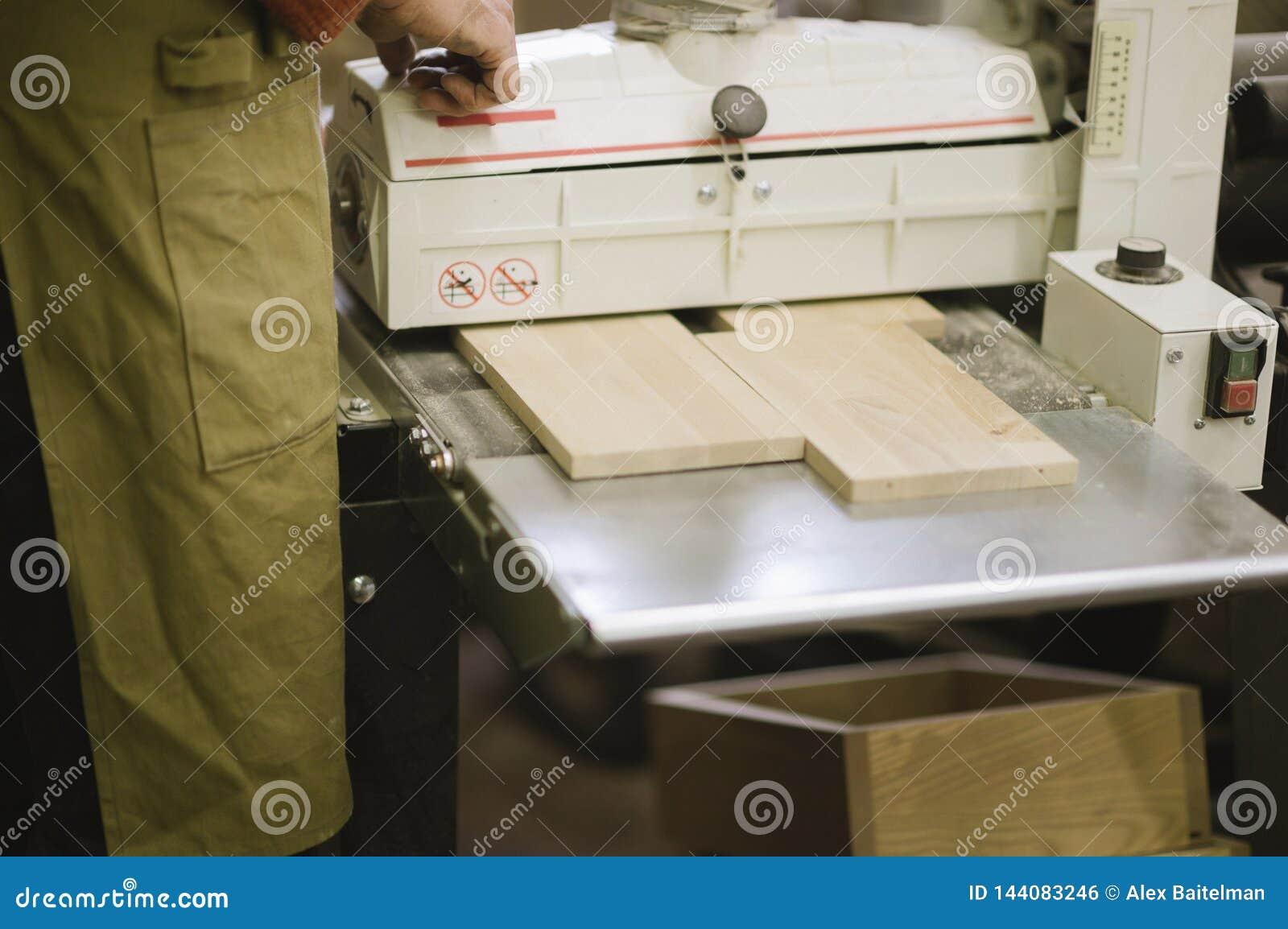 De meester werkt aan een vlakslijpenmachine in de timmerwerkworkshop