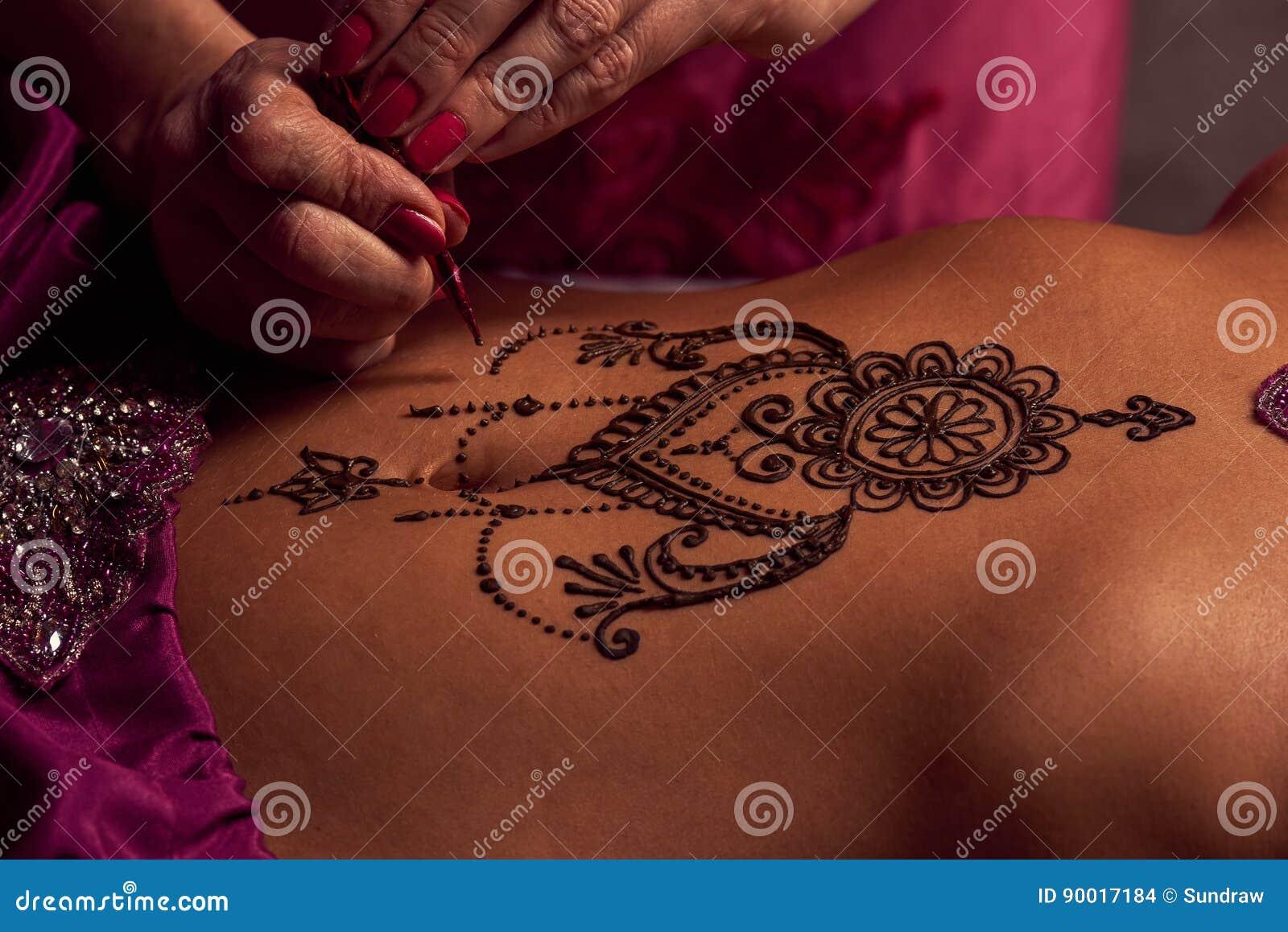 De Mehendikunstenaar schildert een ornament van henna op een oostelijke mooie girl'smaag