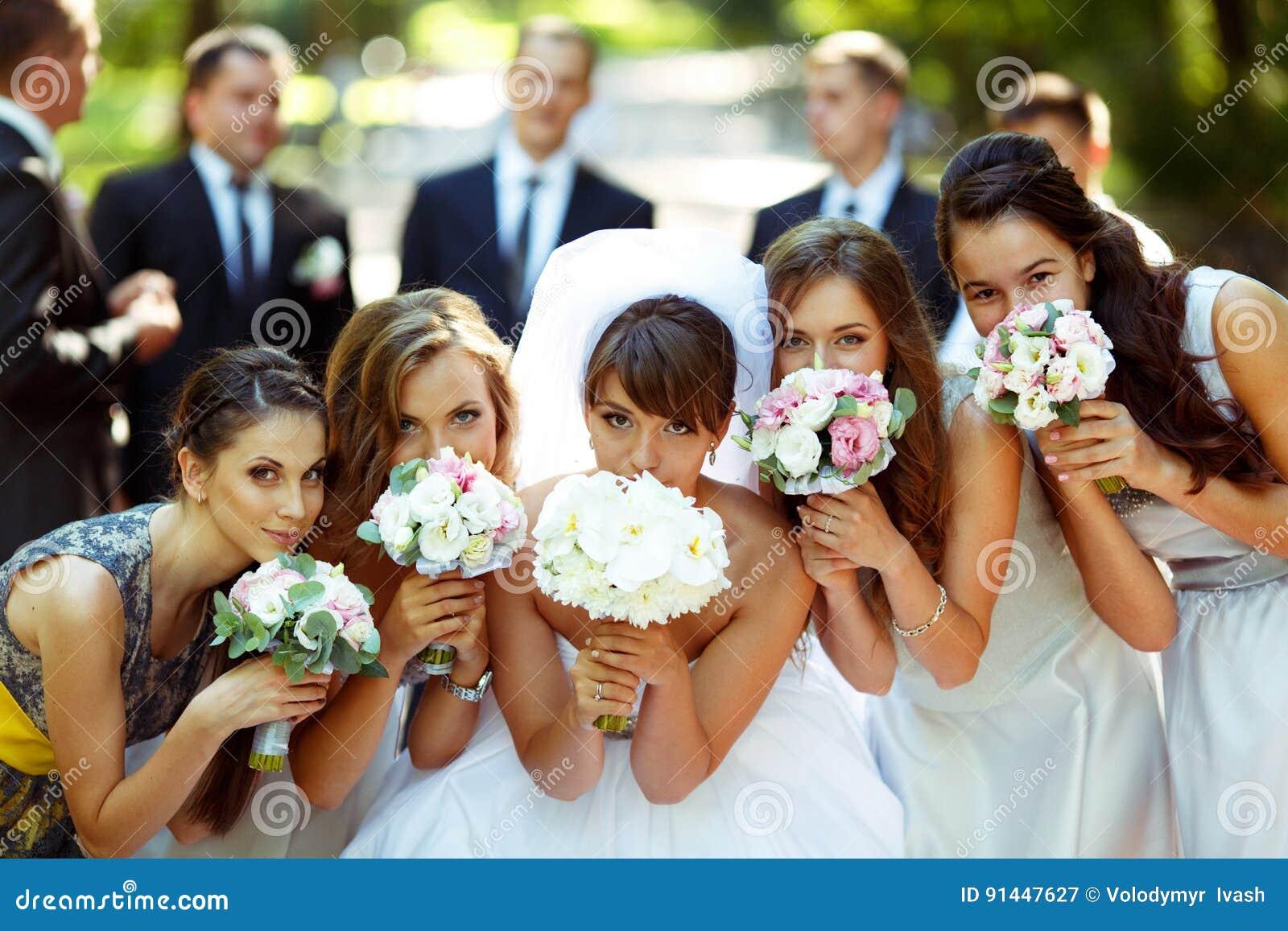 De meisjes en de bruid stellen met huwelijksboeketten terwijl bruidegom en bruidegom
