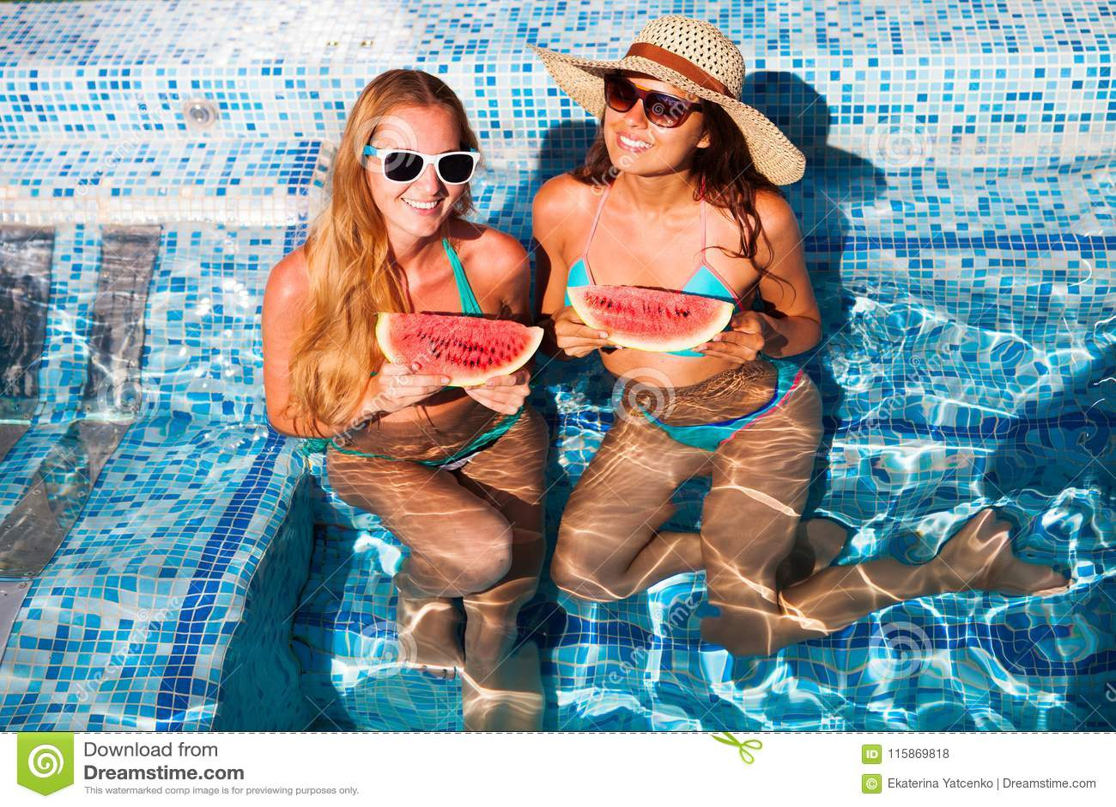 De meisjes houdt de helft van een rode watermeloen over een blauwe pool, ontspannen