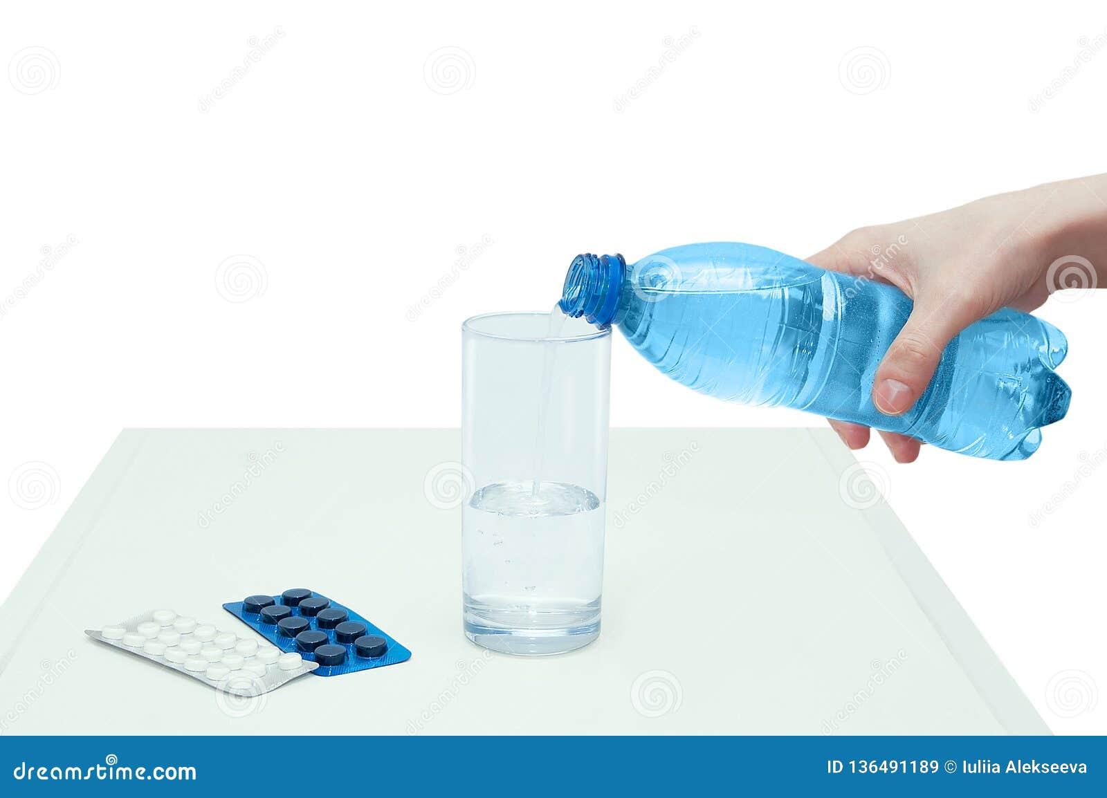 De meisjeshand giet water van de fles in het glas Nabijgelegen lig verpakking met tabletten