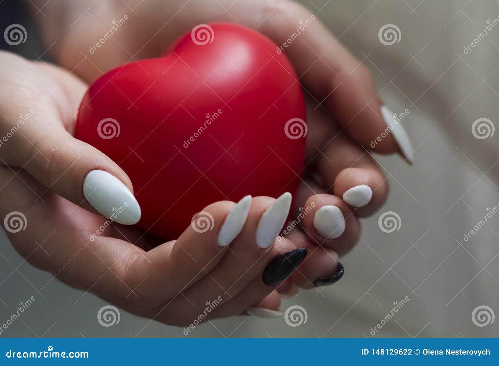 De meisjeshanden die rood hart, gezondheidszorg, schenken en het concept van de familieverzekering, de dag van het wereldhart, de