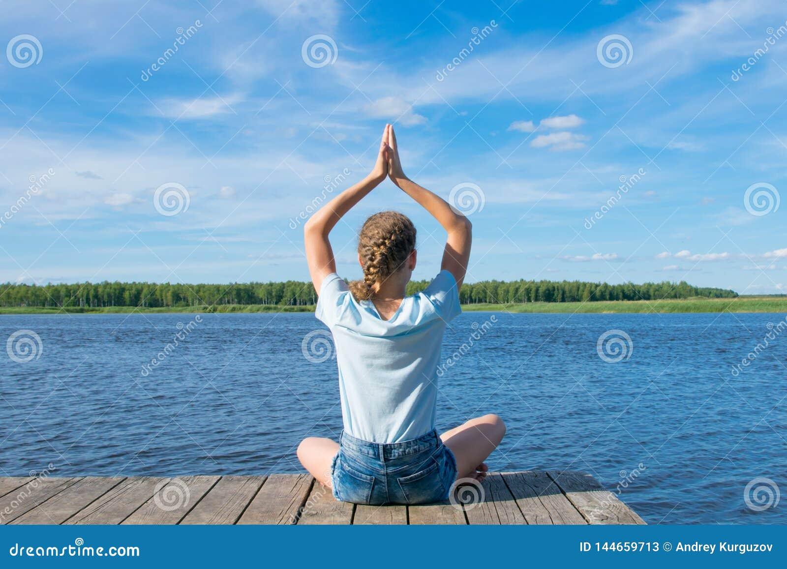De meisjeszitting op de pijler, die zijn handen opheffen omhoog, nam in meditatie in dienst, tegen het meer