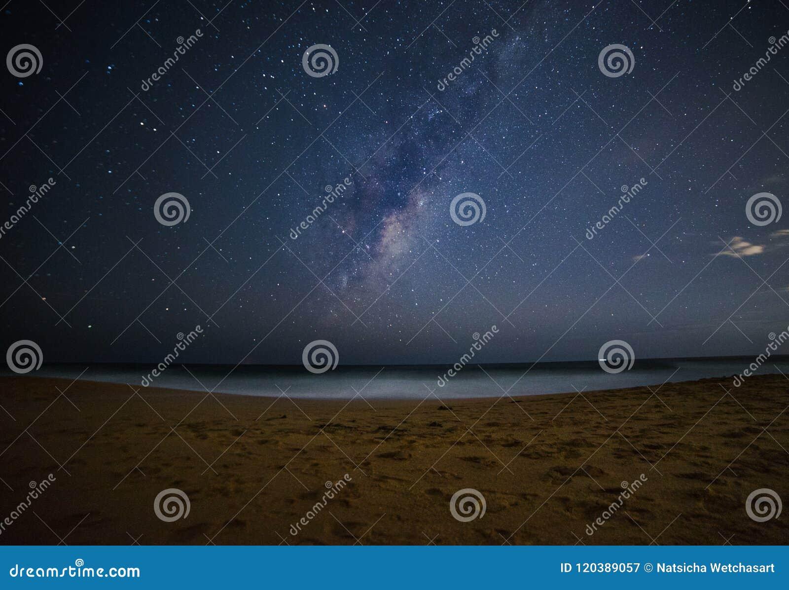 De melkachtige manier glanst over het overzeese strand bij nacht