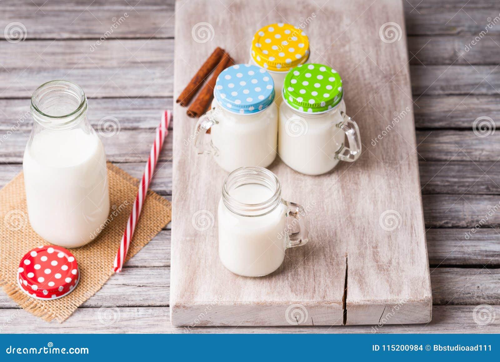 De melkkruiken met kleurrijke kappen op een knipsel schepen, kaneel en het drinken stro in