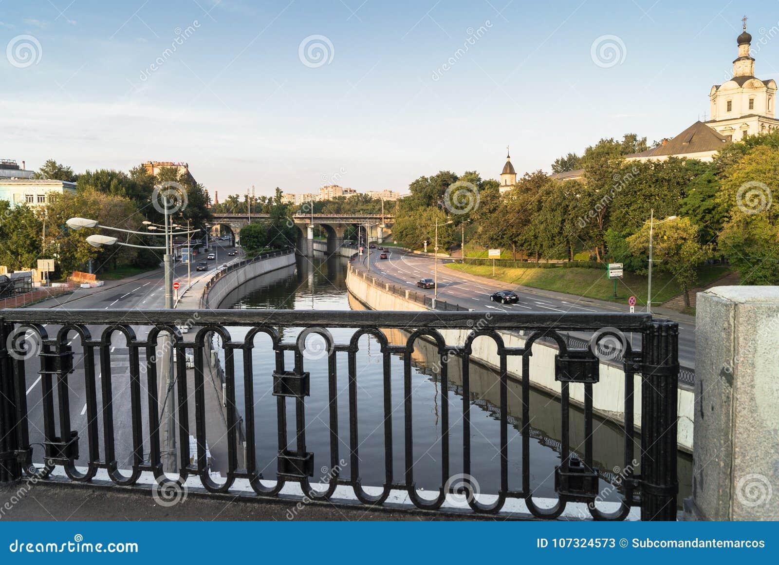 De mening van de rivier Yauza en de rijweg van zijn dijken van Kostomarovsky overbruggen in zonsonderganglicht, Moskou, Rusland