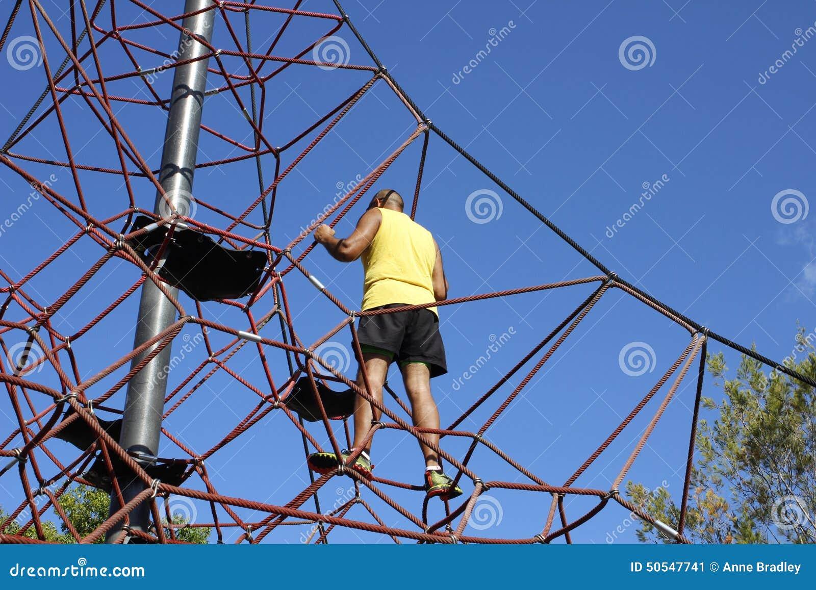 De mens beklimt tot de bovenkant van een klimrek van kinderen