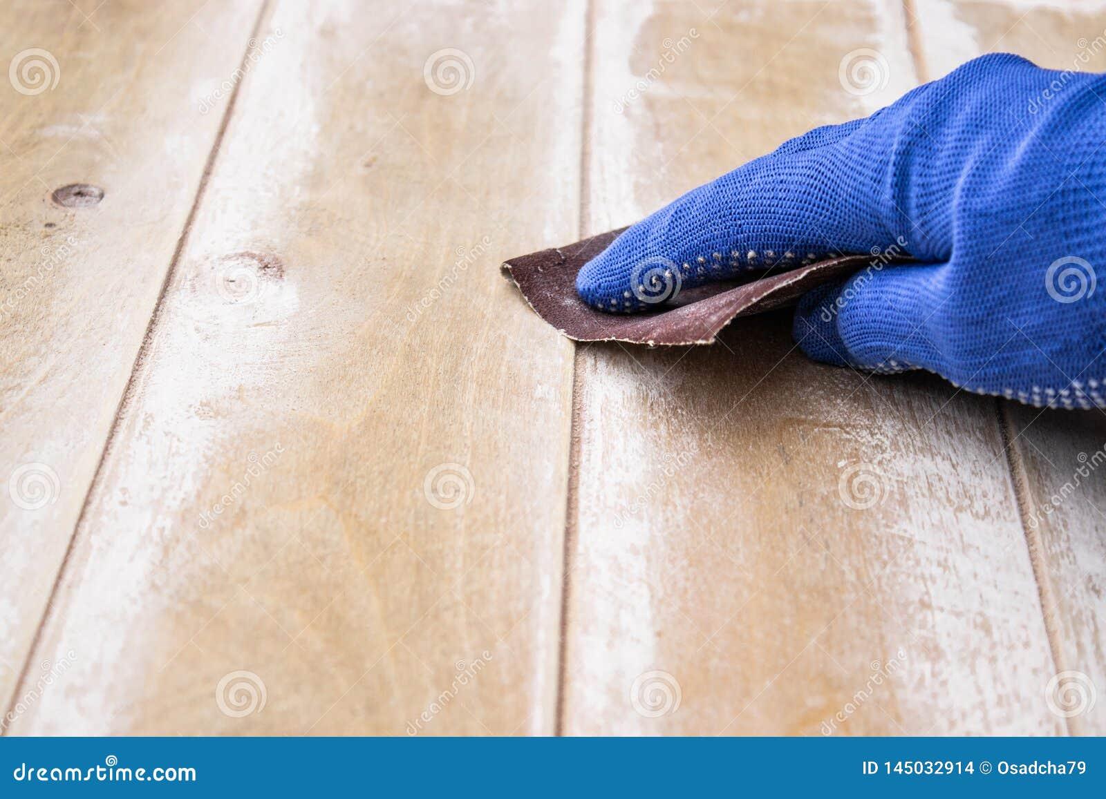 De mens bereidt de oppervlakte voor het schilderen van en het malen van handen voor