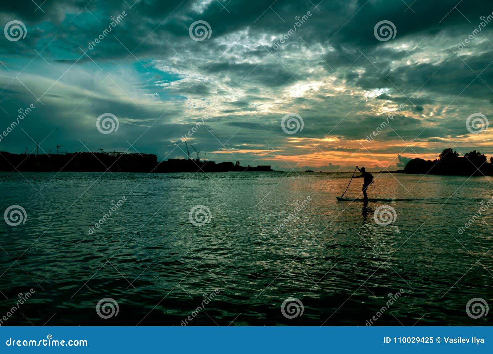 De mens is bezig geweest met watersporten in de avond