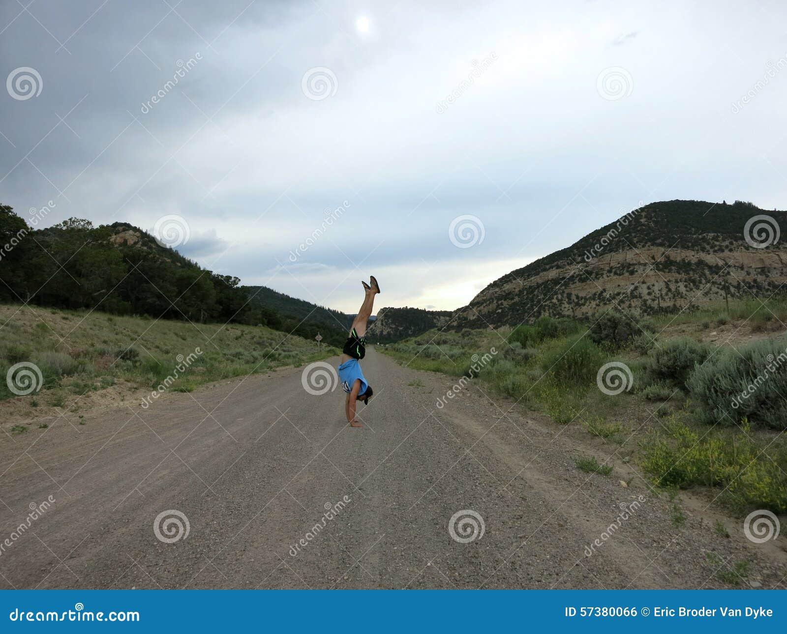 De mens die een hoed, een t-shirt, borrels, en pantoffels dragen doet Handstanden