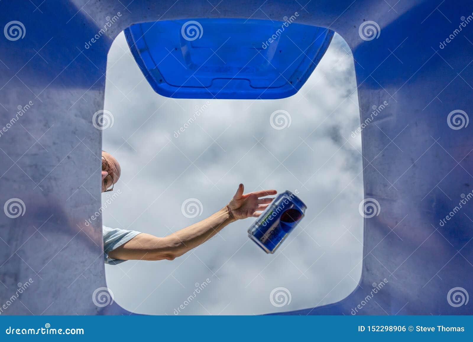 De mens die frisdrank laten vallen kan in blauwe recyclings wheelie bak